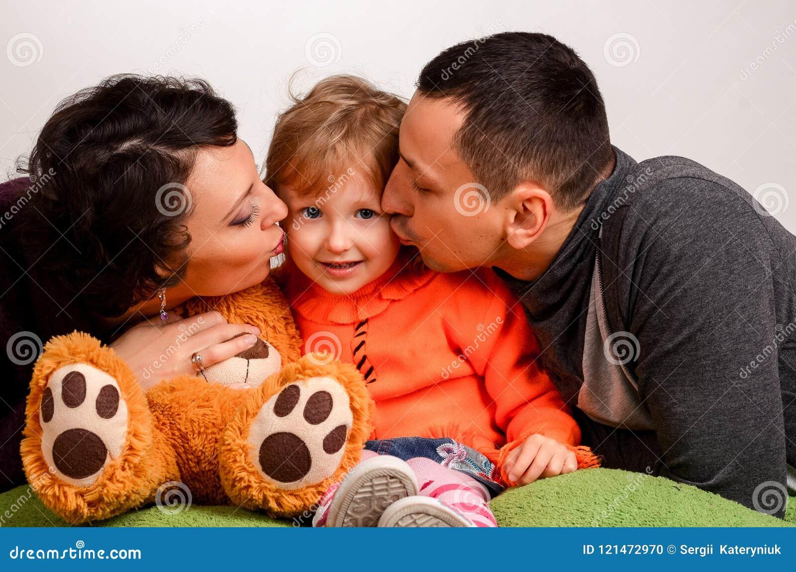Föräldrar kysser den lilla dottern på en vit bakgrund