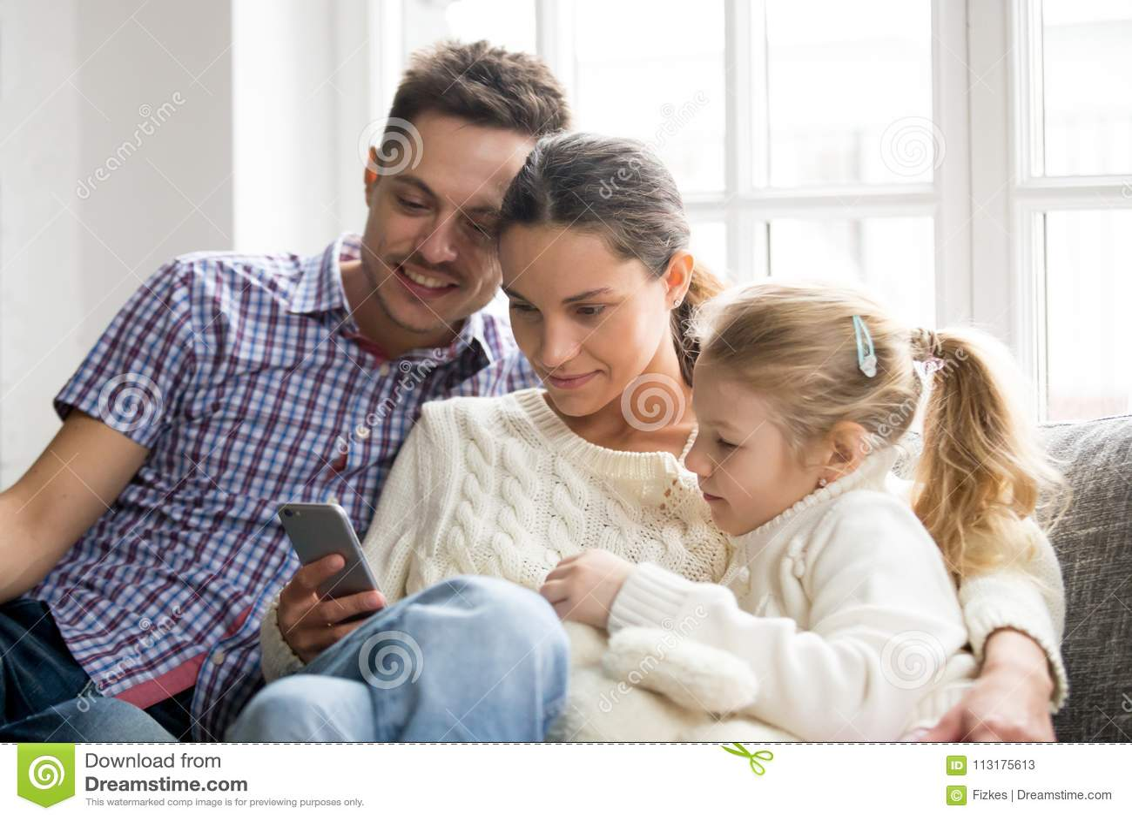 Föräldrar med hållande ögonen på video för dotter på mobiltelefonen hemma