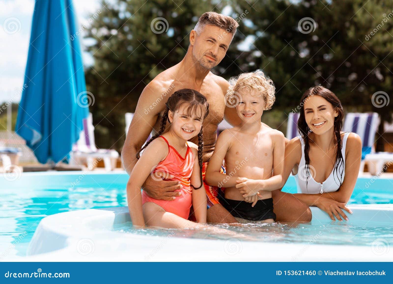 Föräldrar och barn som tillsammans tycker om semester i simbassäng