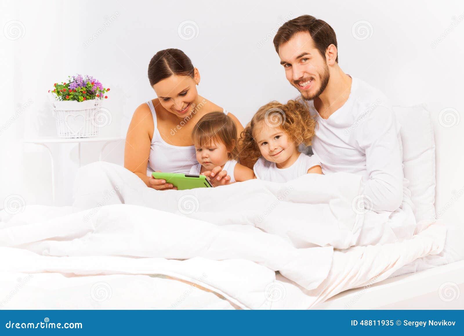 Föräldrar och två ungar spelar med minnestavlan på vit säng
