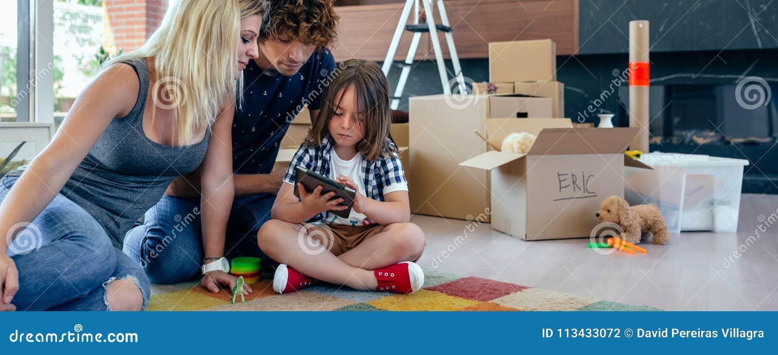 Föräldrar som övervakar deras lilla son spela minnestavlan