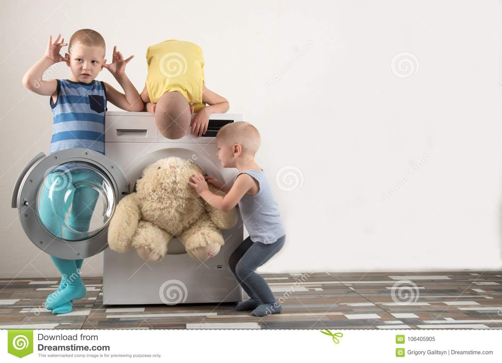 Föräldrar som köps en ny tvagningmaskin Barnen försöker att vända på det och att tvätta de mjuka leksakerna Lyckliga pojkar spela