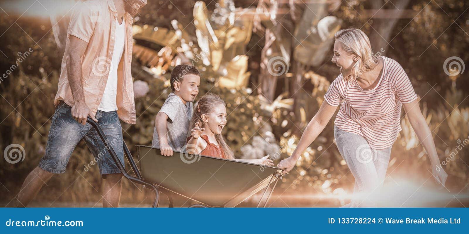 Föräldrar som skjuter barn som sitter i skottkärra på gården