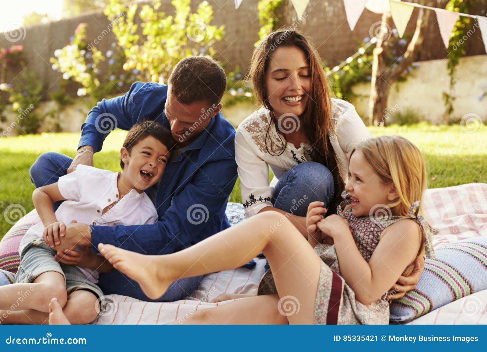 Föräldrar som spelar leken med barn på filten i trädgård