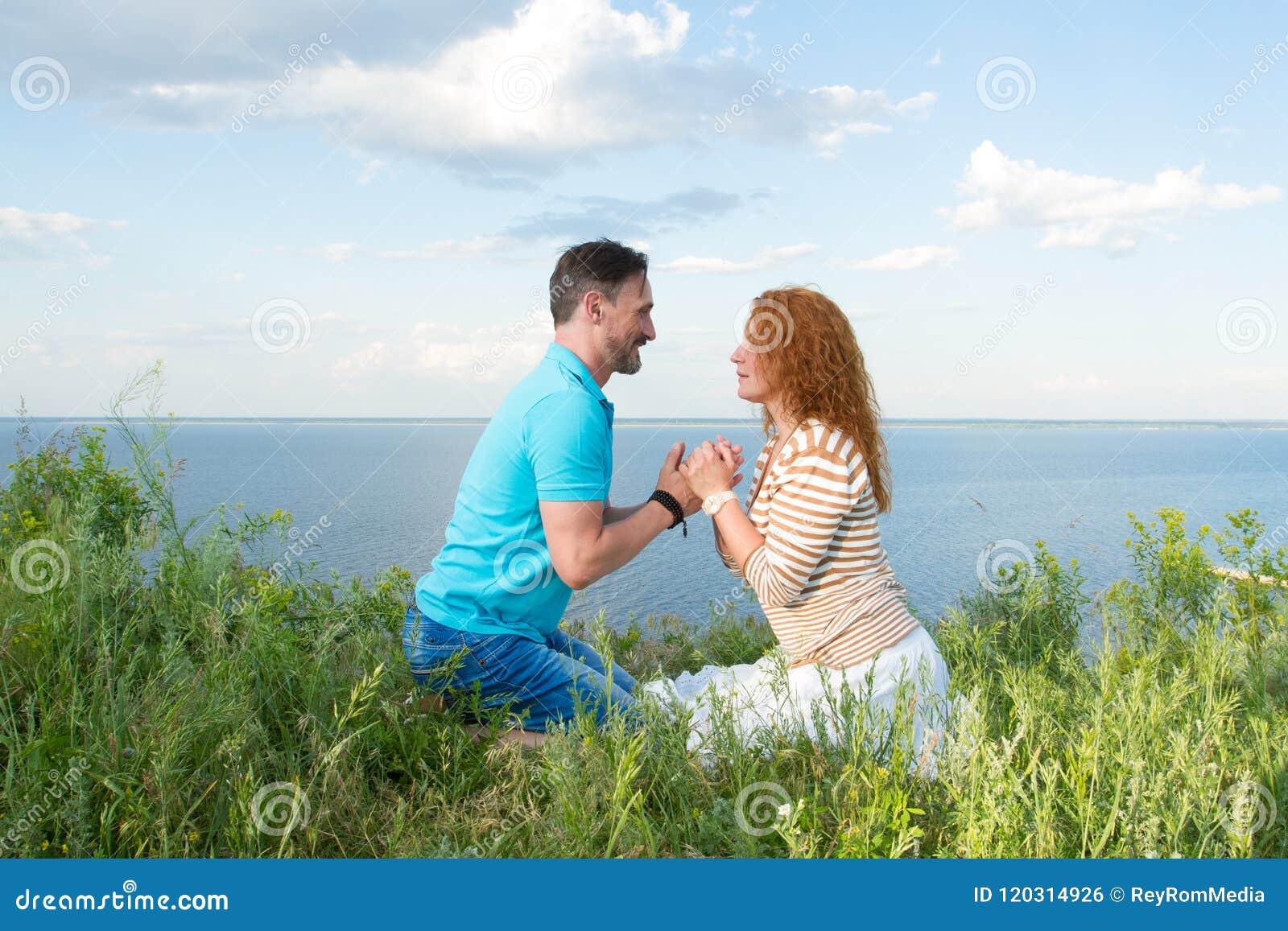 Förälskade flörtar för par på stranden Grabben rymmer flickahänderna och tilldrar till honom Ståenden av ett lyckligt kopplar iho