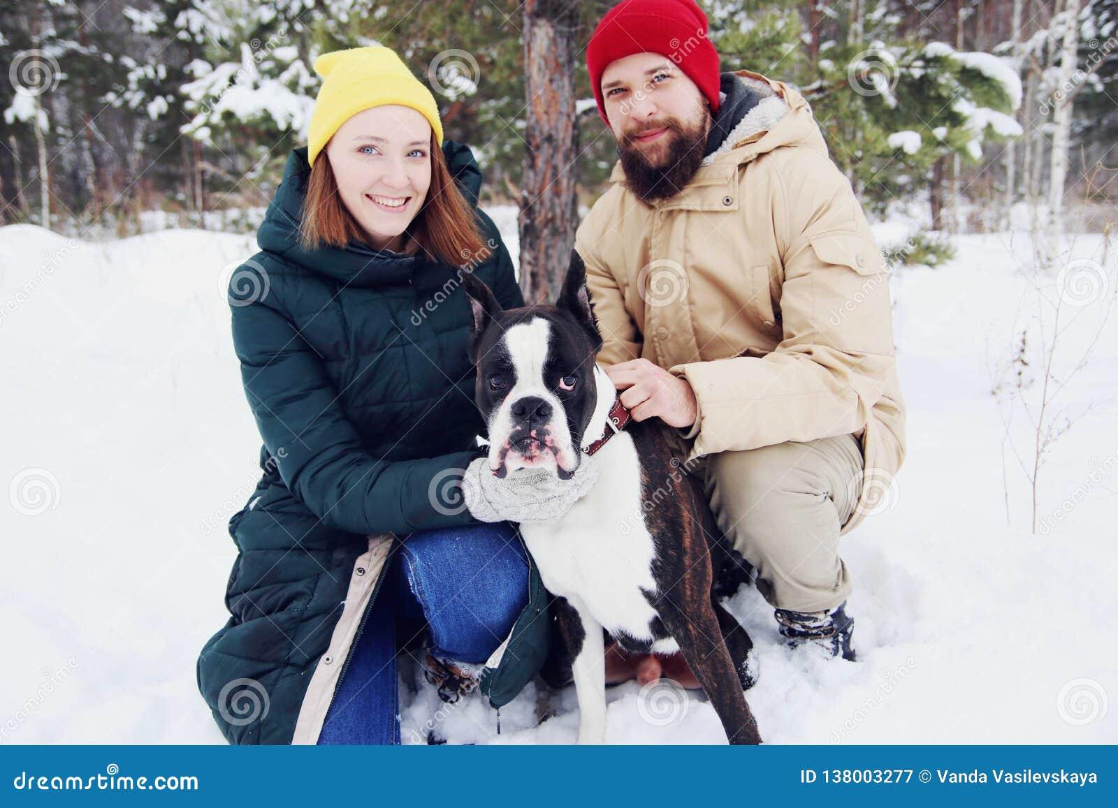 Förälskade lyckliga par ha gyckel i snön med hans behandla som ett barn hunden