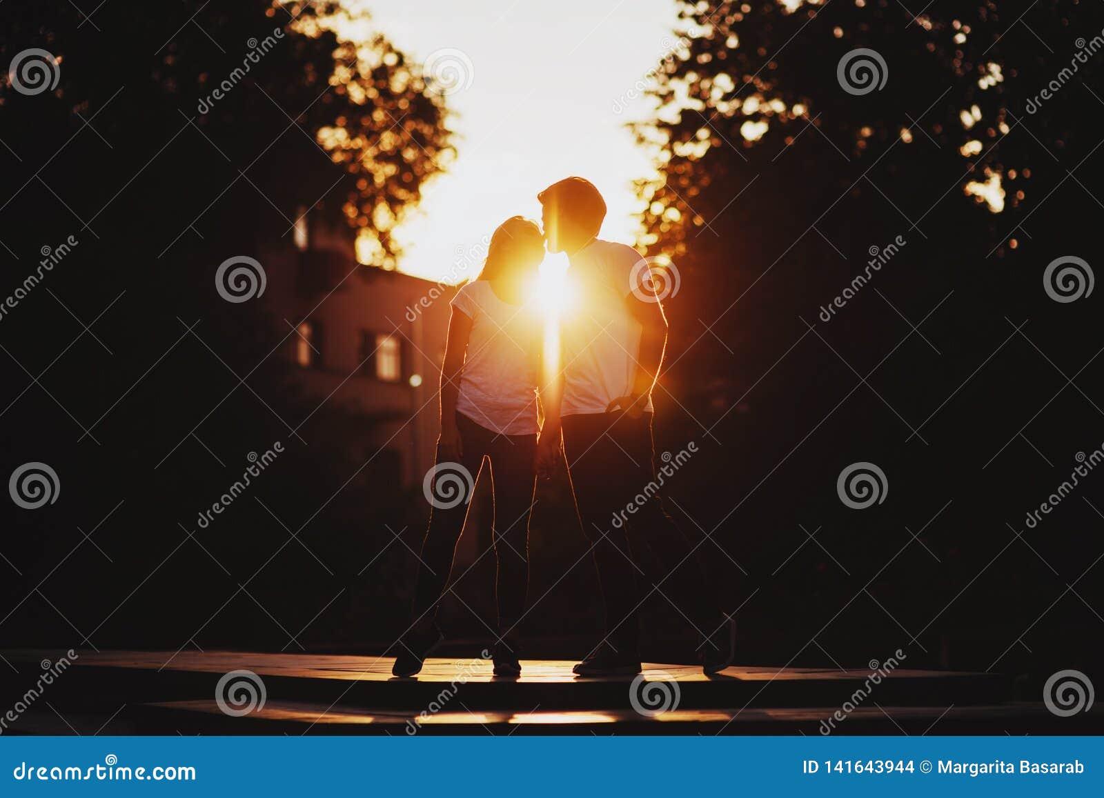 Förälskade tyckande om ögonblick för par under solnedgång
