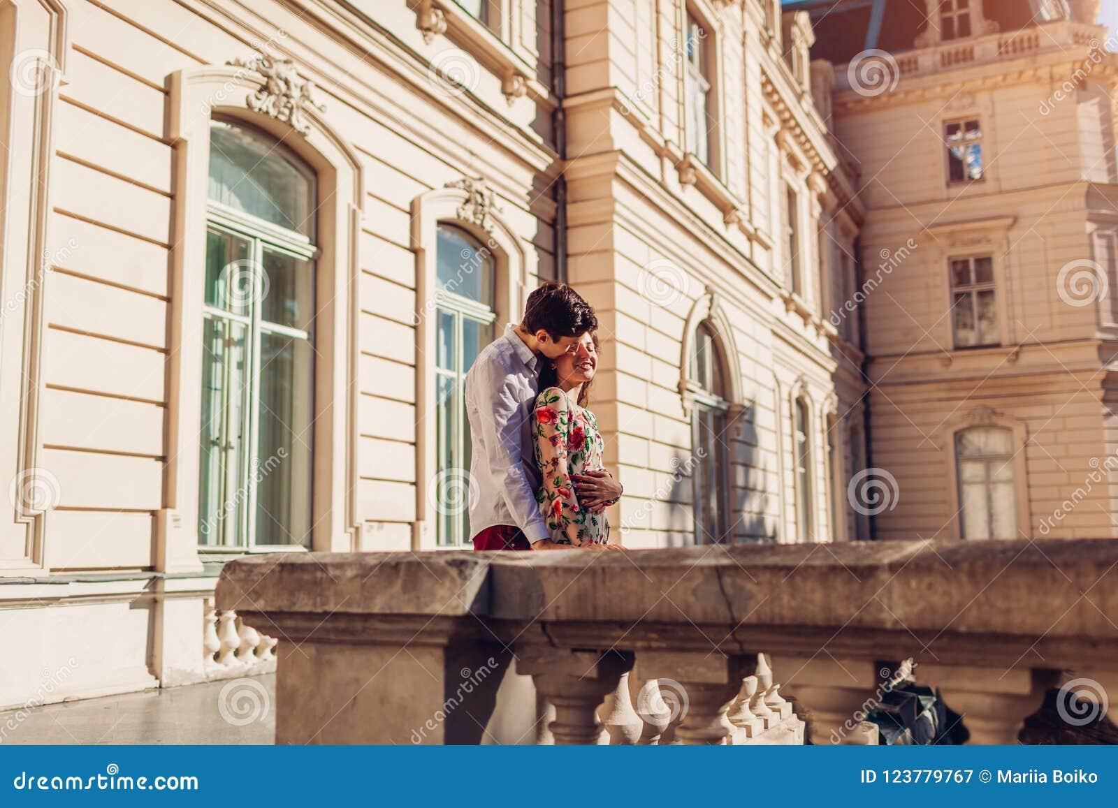Förälskat krama för unga lyckliga par utomhus Romantisk man och kvinna som går vid gammal stadsarkitektur