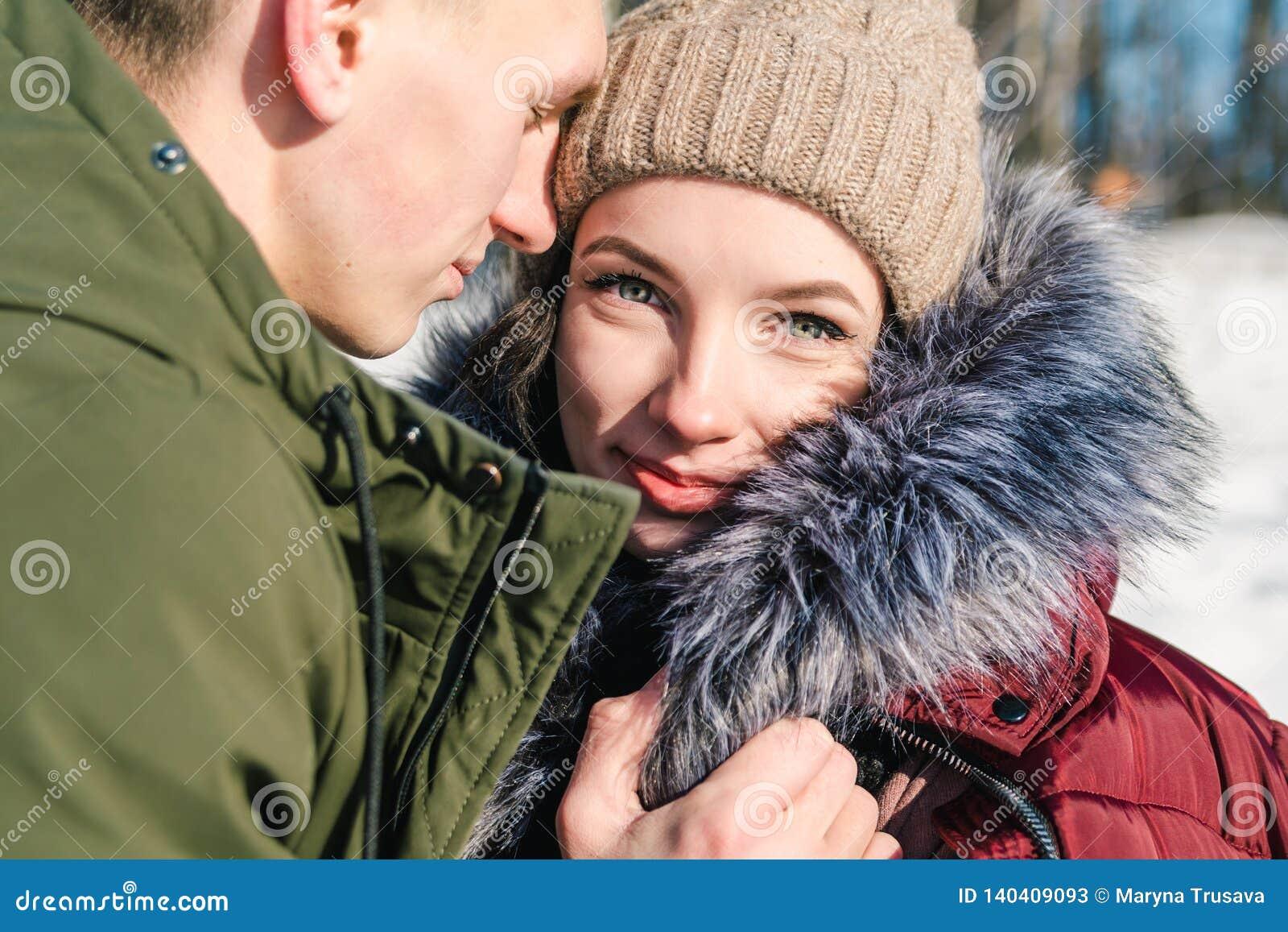 Förälskat parkerar krama för härliga unga par i på en klar solig vinterdag