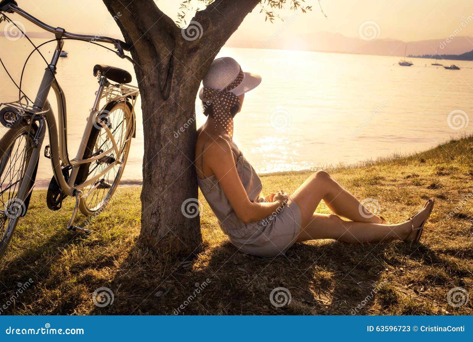 Förälskat vänta för härlig kvinna under en olivträd på solnedgången