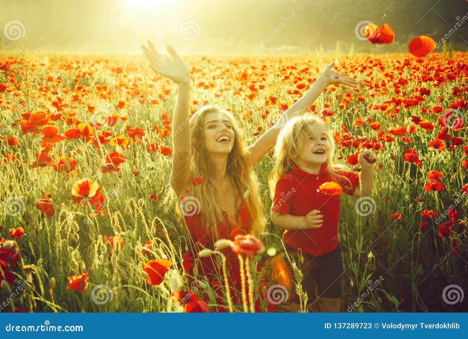 Förälskelse och familj, lycklig moder och barn i vallmofält