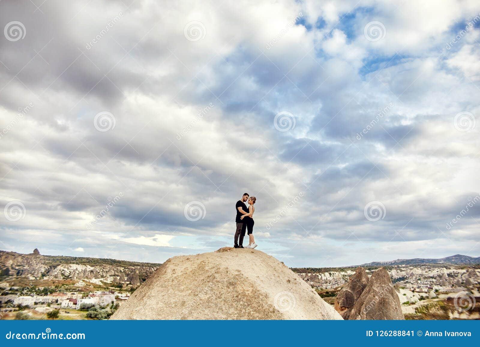 Förälskelse och sinnesrörelser som älskar par som vilar i Turkiet Det förälskade östliga paret i bergen av Cappadocia kramar och