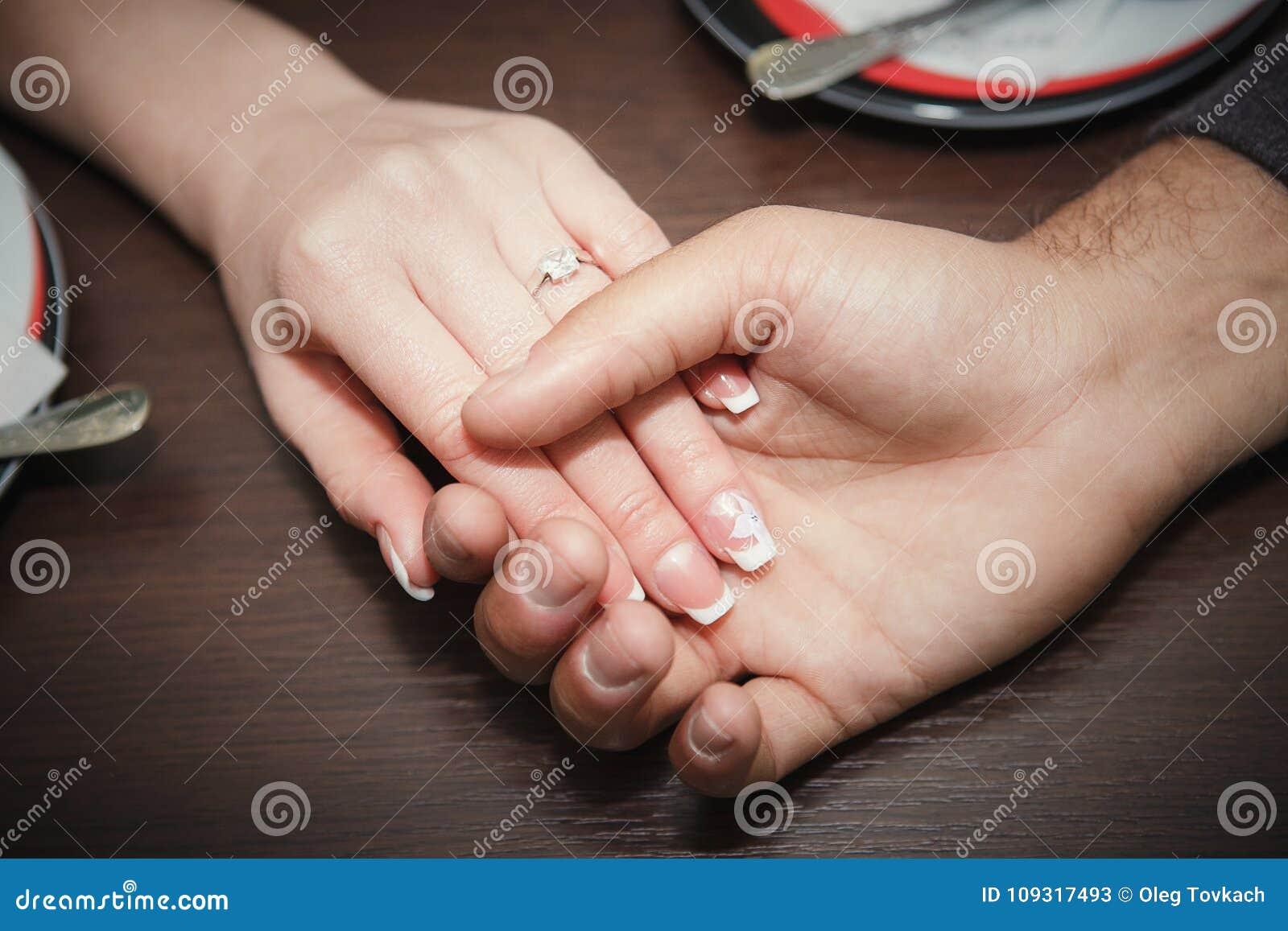 Förälskelsebegrepp - som är nära av förlovade parinnehavhänder med diamantcirkeln över ferier, tänder upp bakgrund