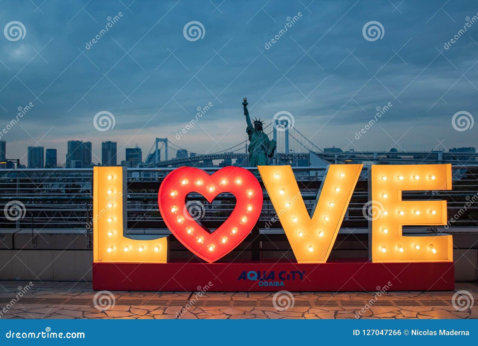 Förälskelsetecken med ljus, den japanska statyn av frihet och regnbågebron på den blåa timmen