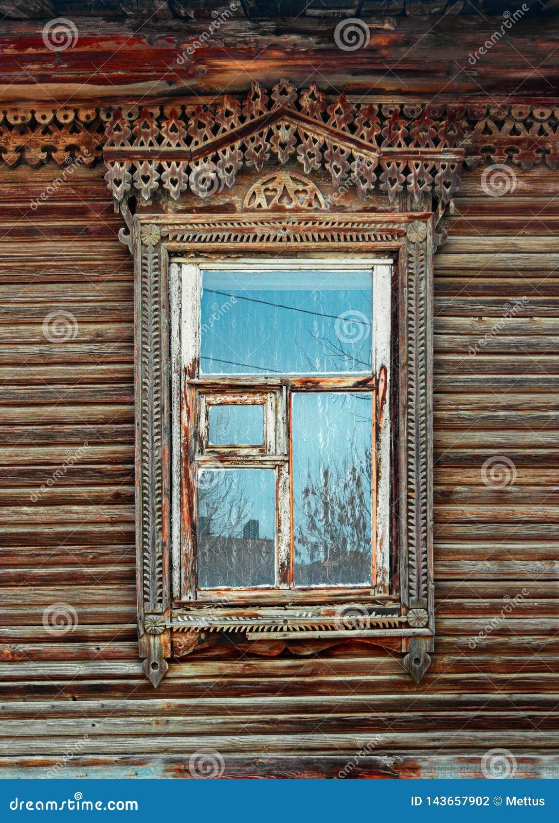 Föråldrat utsmyckat snidit träfönster i gammal ryssstil