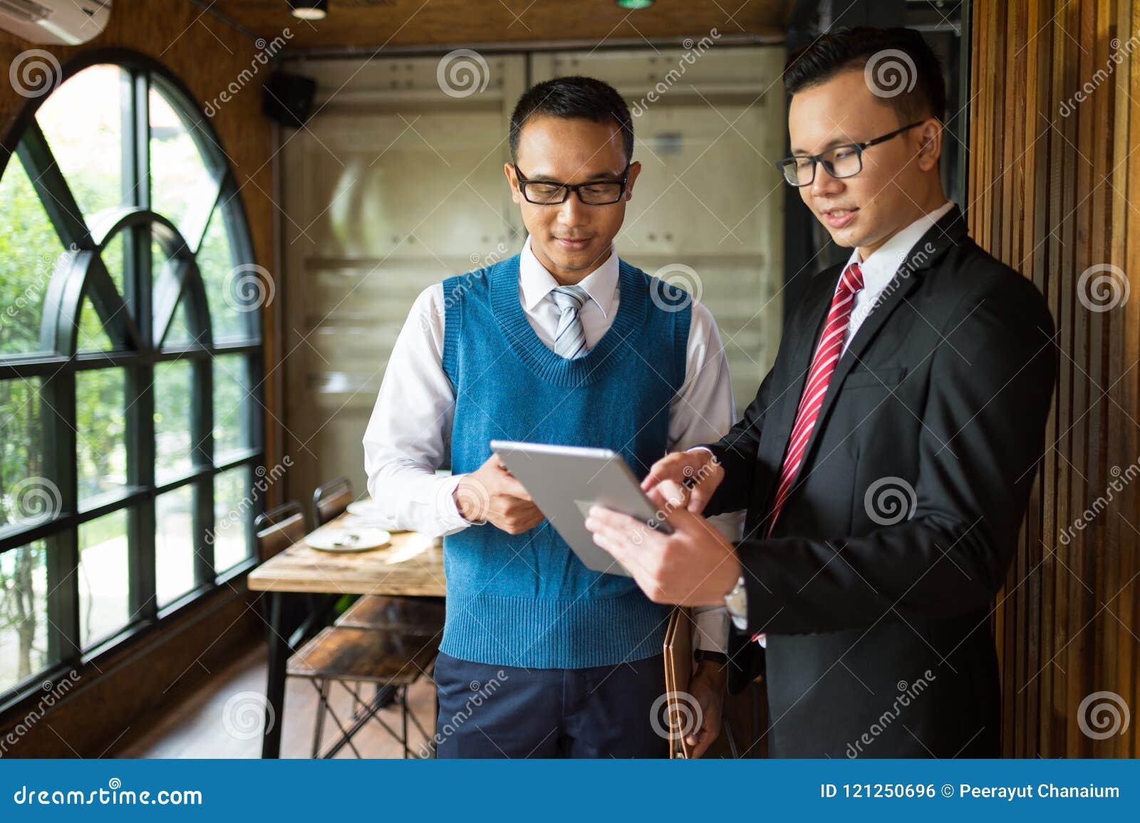 För affärsmanför se och punkt för två asiat fingret för att specificera i anteckningsbok, är de möta och tala om affärsplan