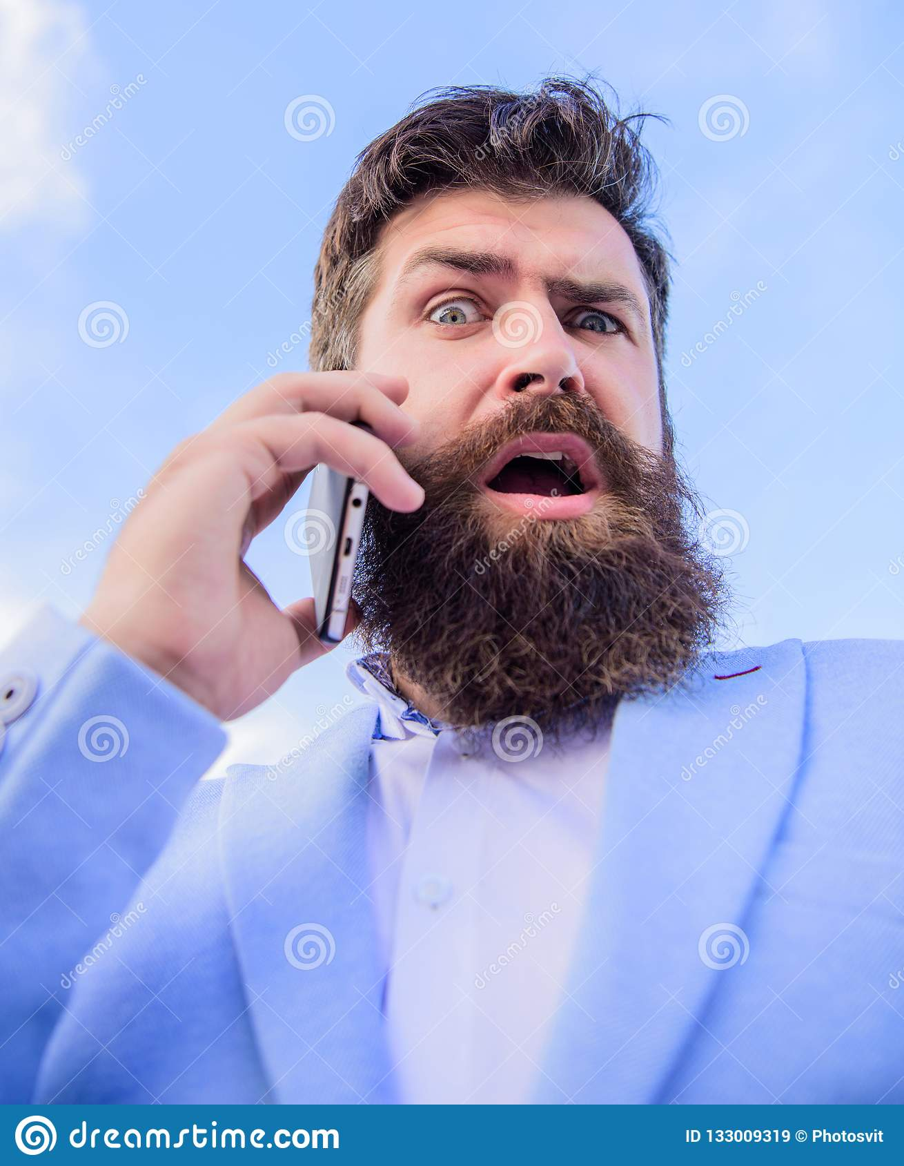 För affärsmanhåll för man skäggig förvånad bakgrund för himmel för mobiltelefon Partner för Hipstersmartphoneappell Mobil appell
