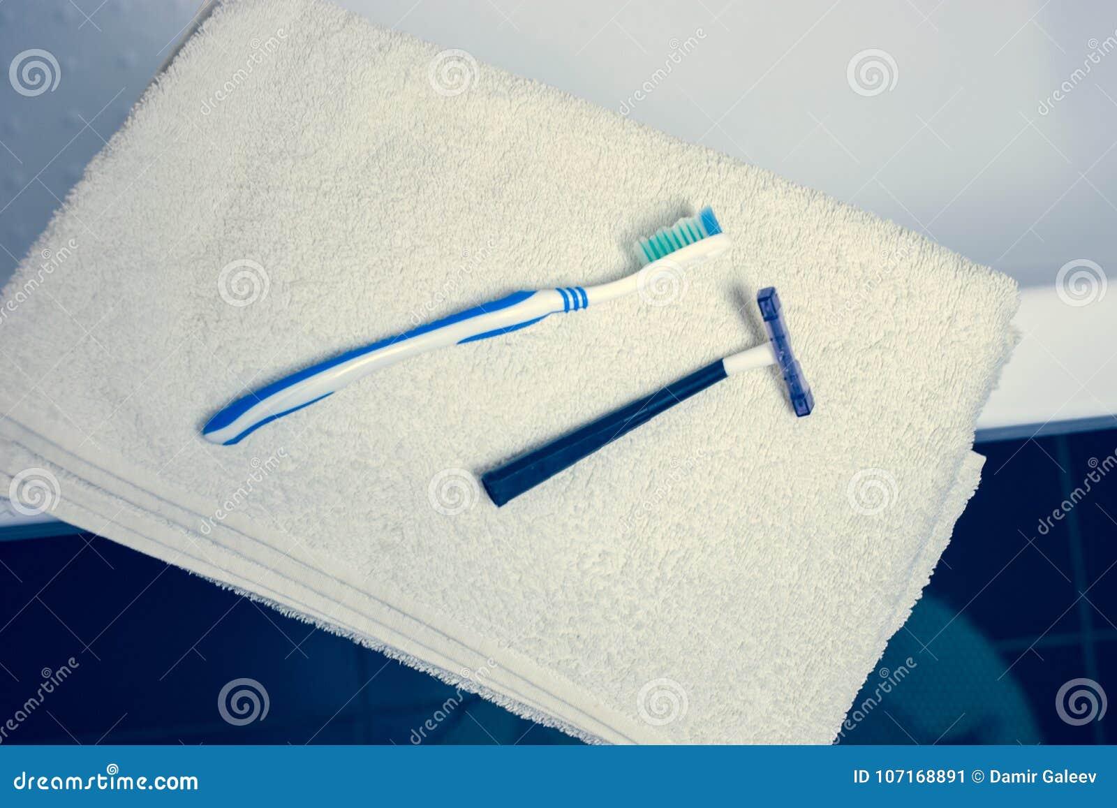 För bakgrunds- och vitbrunnsort för suddigt badrum inre handdukar på marmortandborsterakkniven