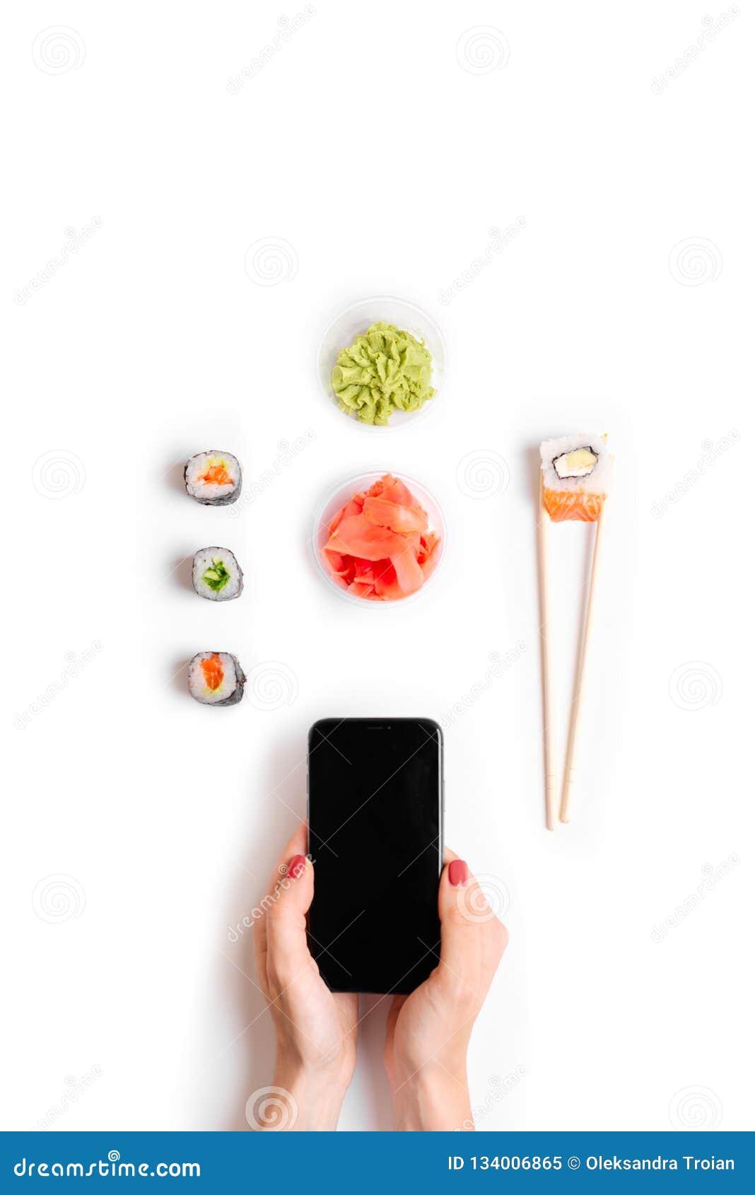 För beställnings- och leveranssushi för japansk restaurang som online-händer för pinnar för rullar rymmer vit bakgrund för bästa