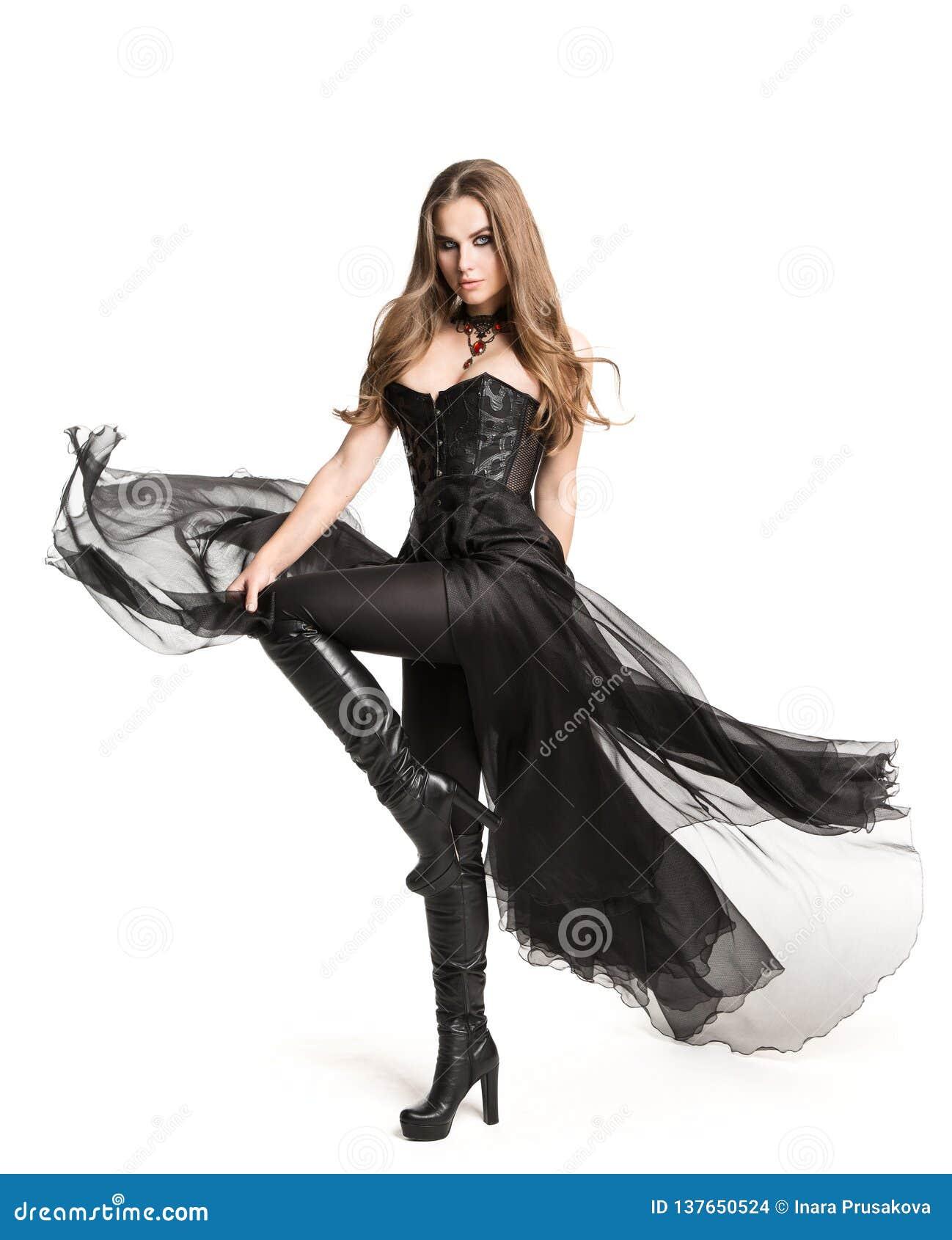 För Black Corset Dress för modemodell kängor läder, härlig kvinna i den gotiska kappan, vit