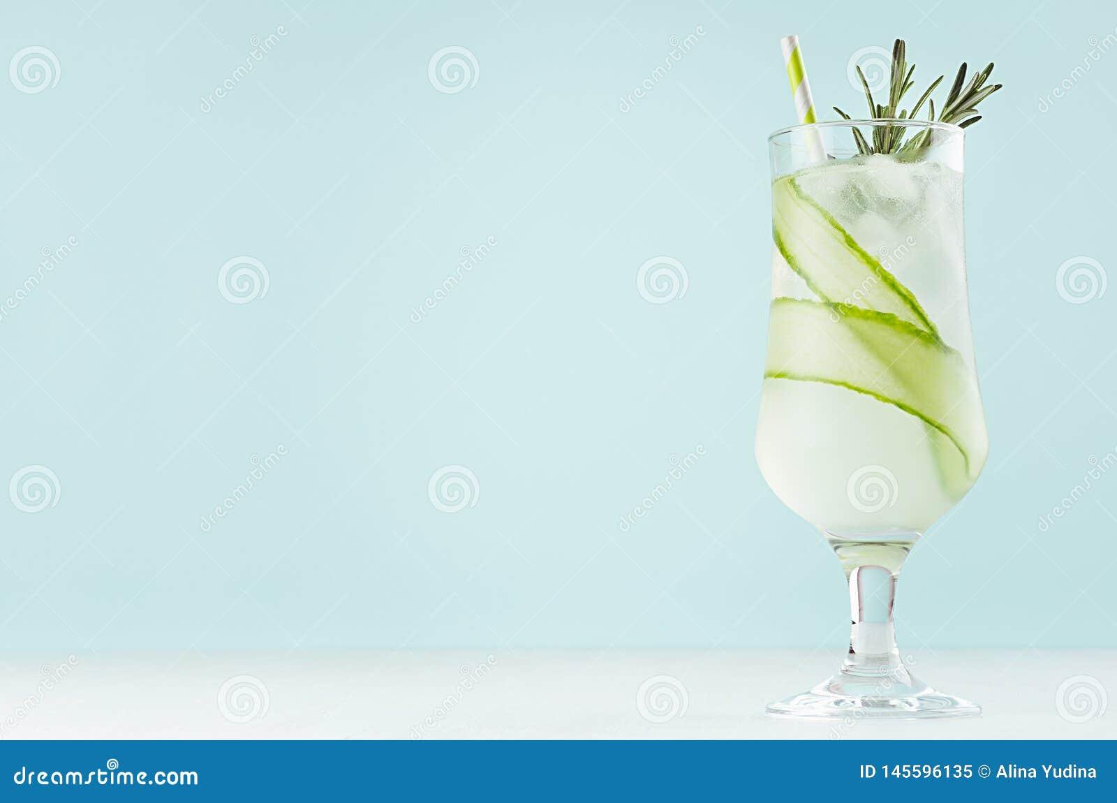 För detoxgurka för sommar ny coctail i vinglas med iskuber, rosmarin, sugrör på pastellfärgad mintkaramellfärgbakgrund, kopiering