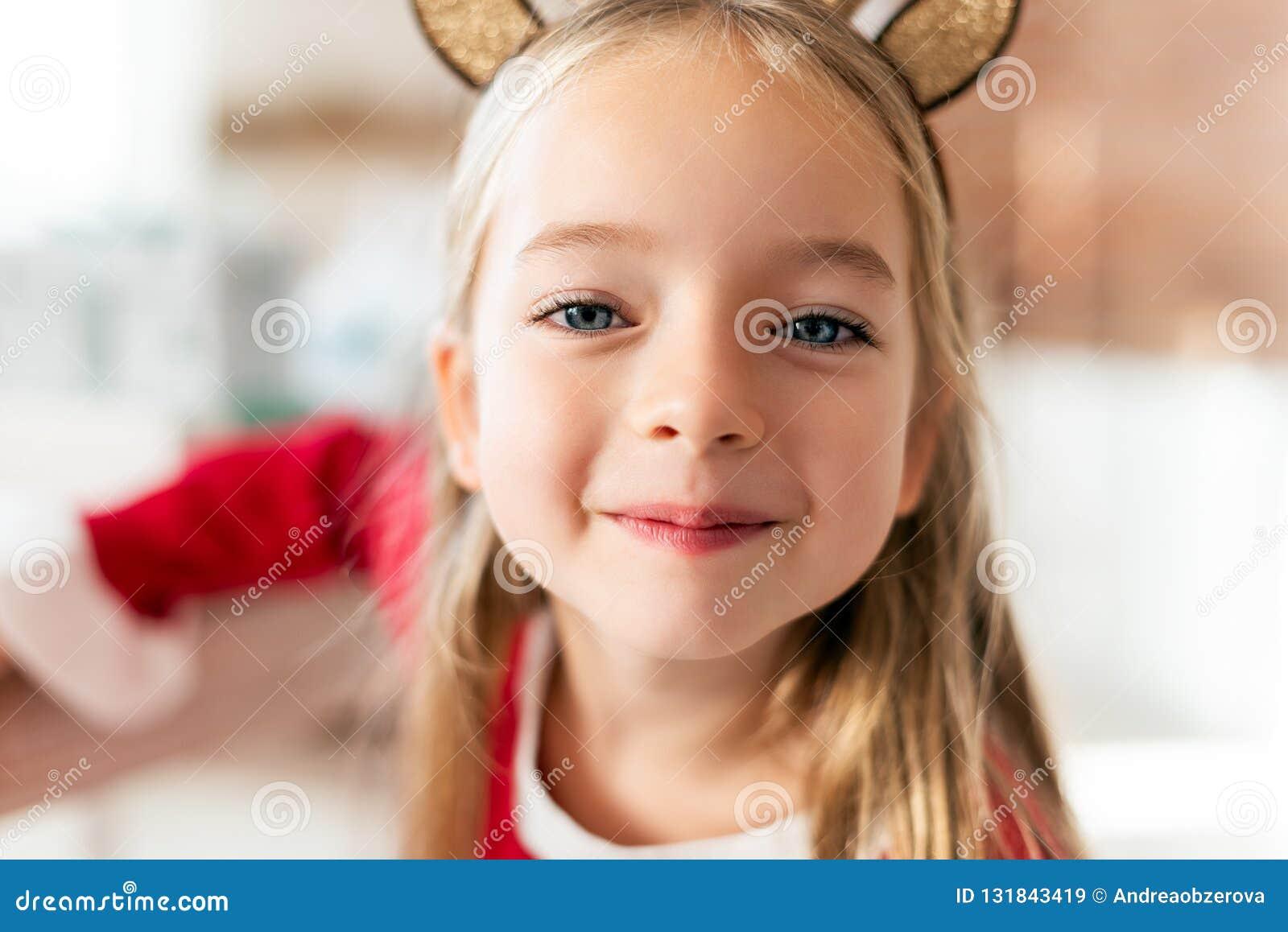 För dräktren för gullig ung flicka bärande horn på kronhjort och att le och se kameran Lycklig unge på jul