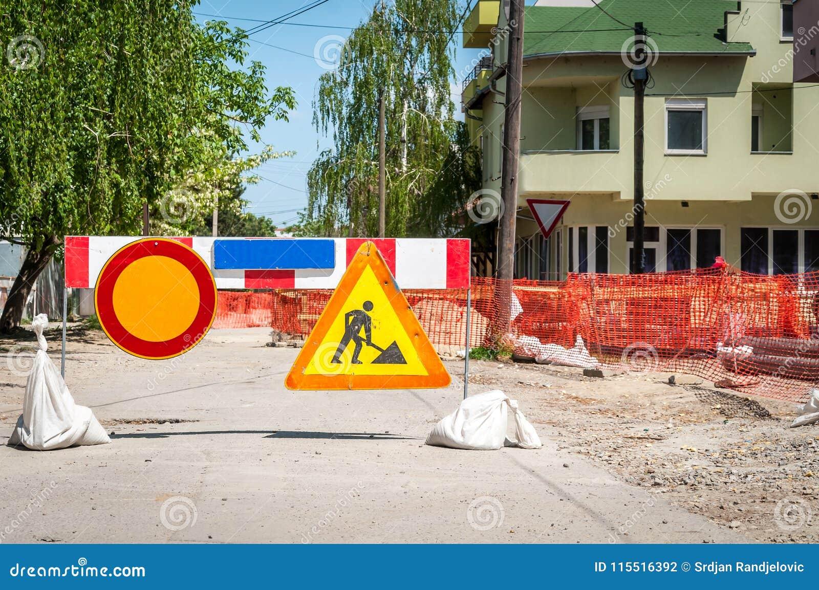 För gatafjärrvärme för arbete framåt plats för rekonstruktion för rörledning med tecknet och staket som vägbarrikaden