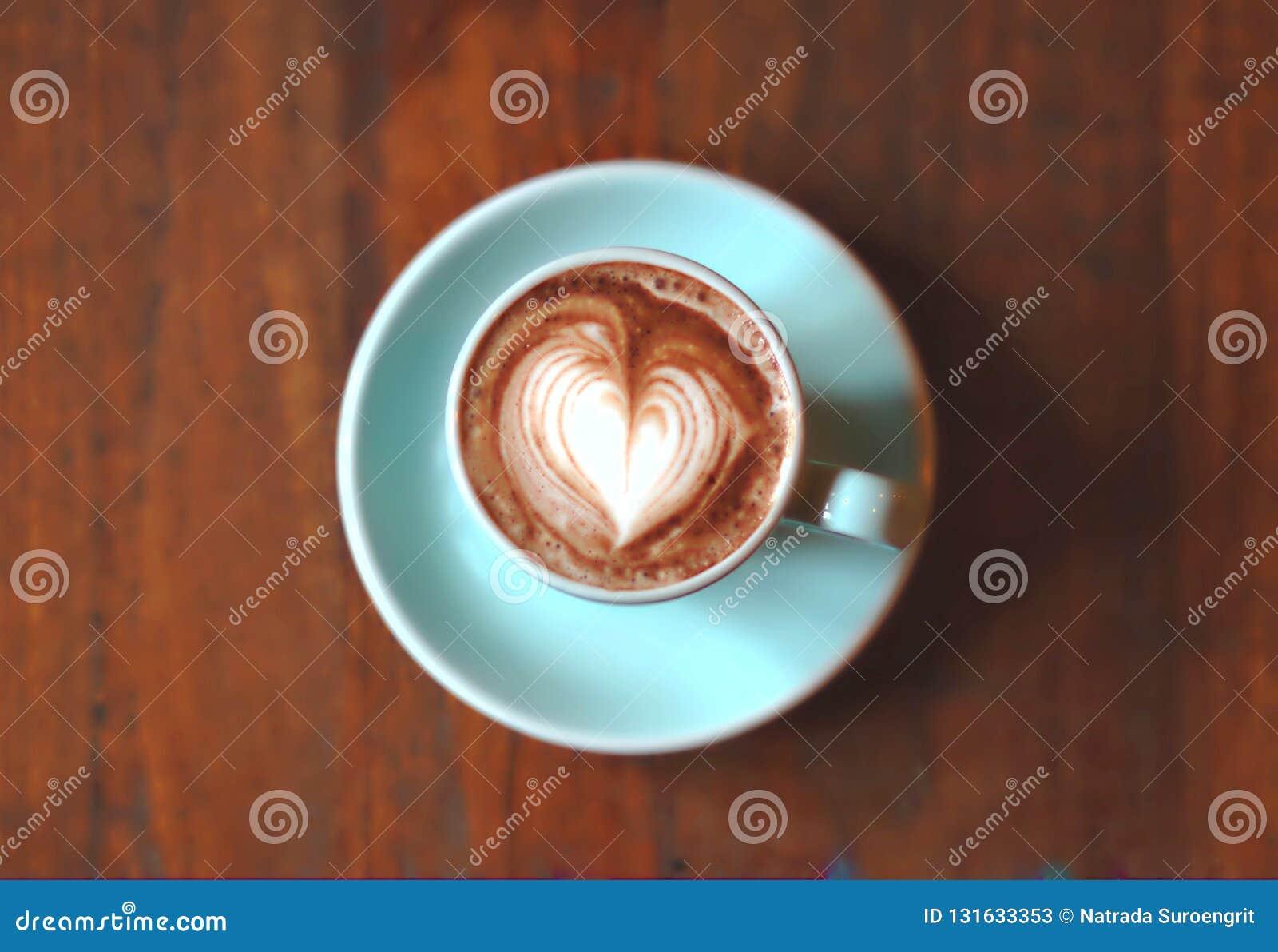 För hjärtalatte för varm choklad konst i blå kopp på trätabellen