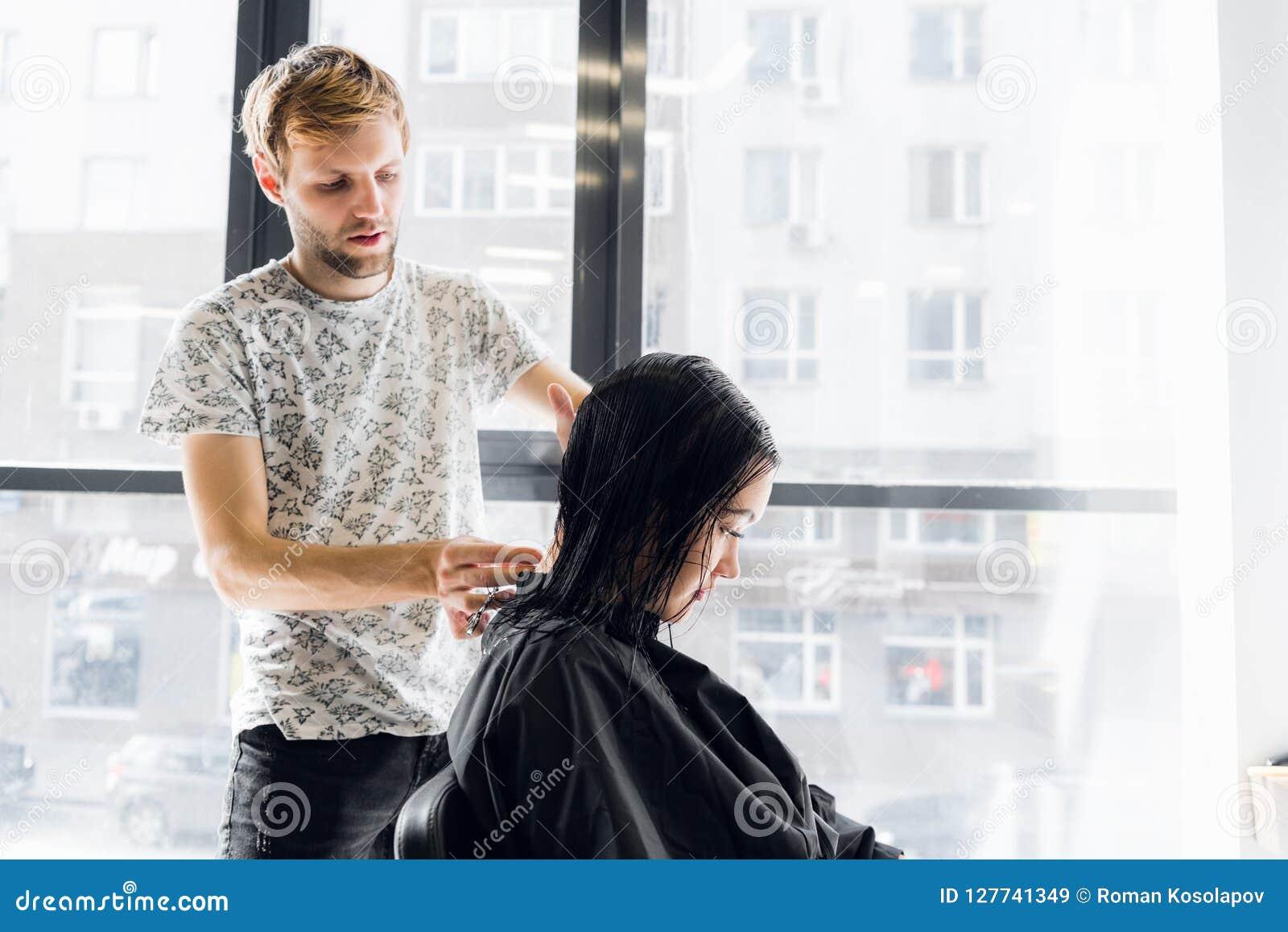 För klient` s för frisör bitande hår i salong med saxcloseupen Använda en hårkam