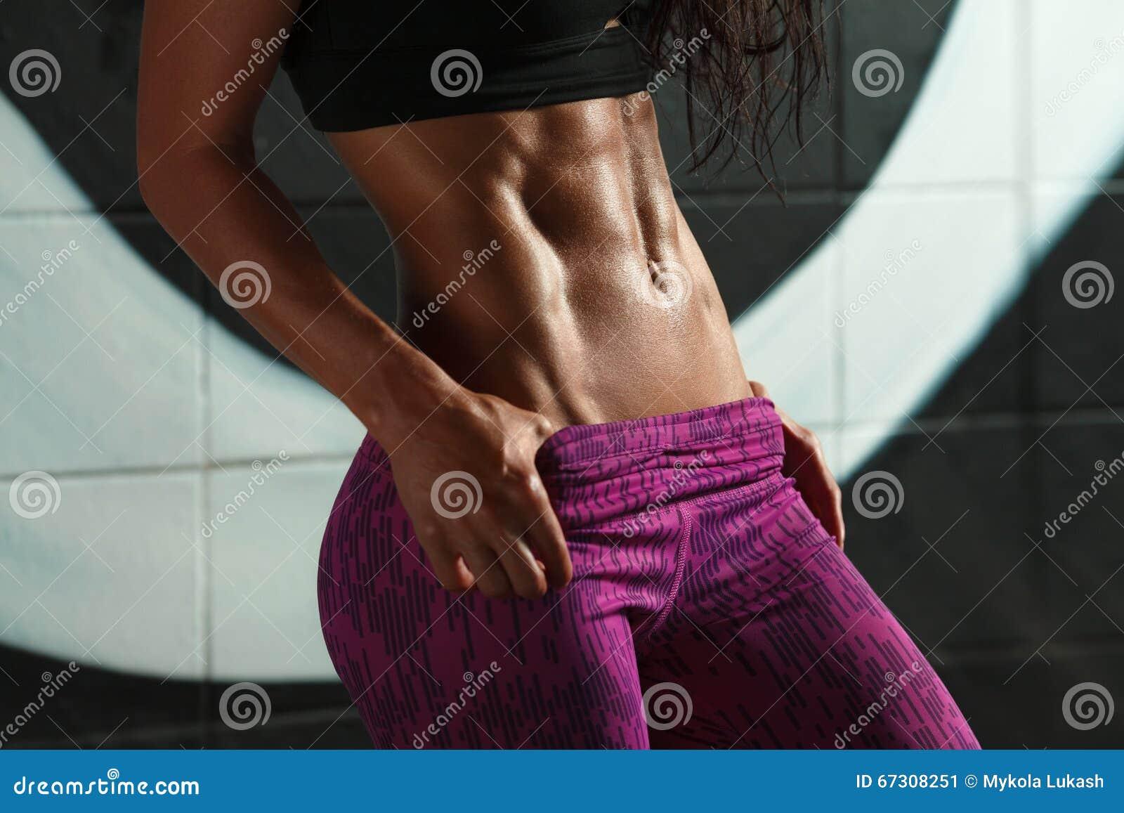 För kvinnavisning för kondition buktar sexiga abs och lägenheten Härlig muskulös flicka, formad buk- slank midja
