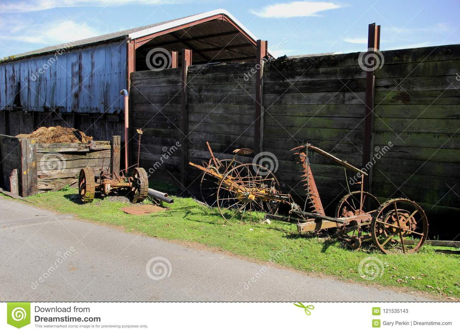 För lantgårdutrustning för tappning som rostigt gammalt ligga är oanvänt på en gräskant I