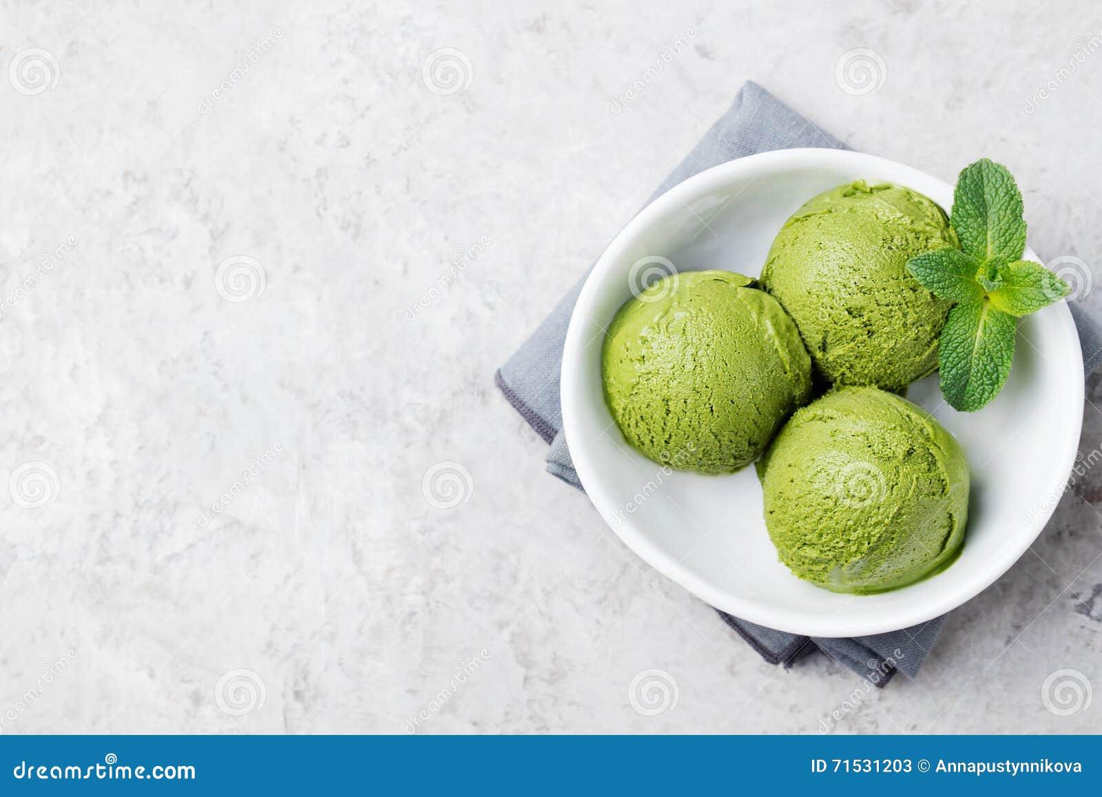För matchaglass för grönt te skopa i den vita bunken på en grå stenbakgrund Bästa sikt för kopieringsutrymme