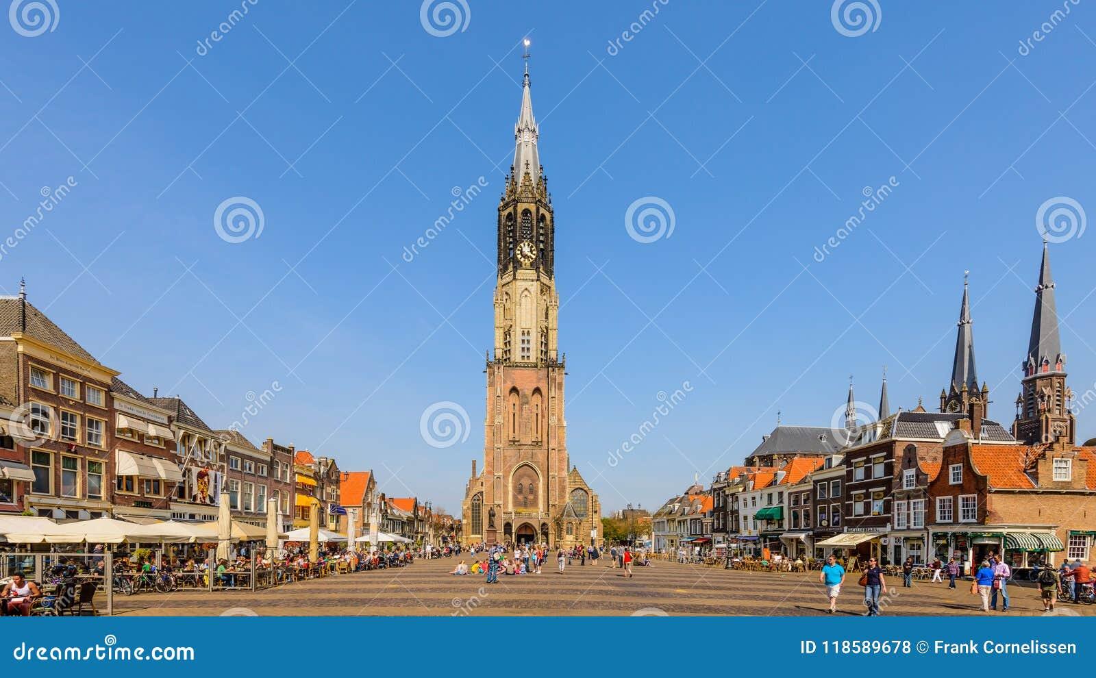 För mittmarknad för delftfajans nederländsk historisk fyrkant med folk som sitter på terrasser som tycker om det härliga vädret