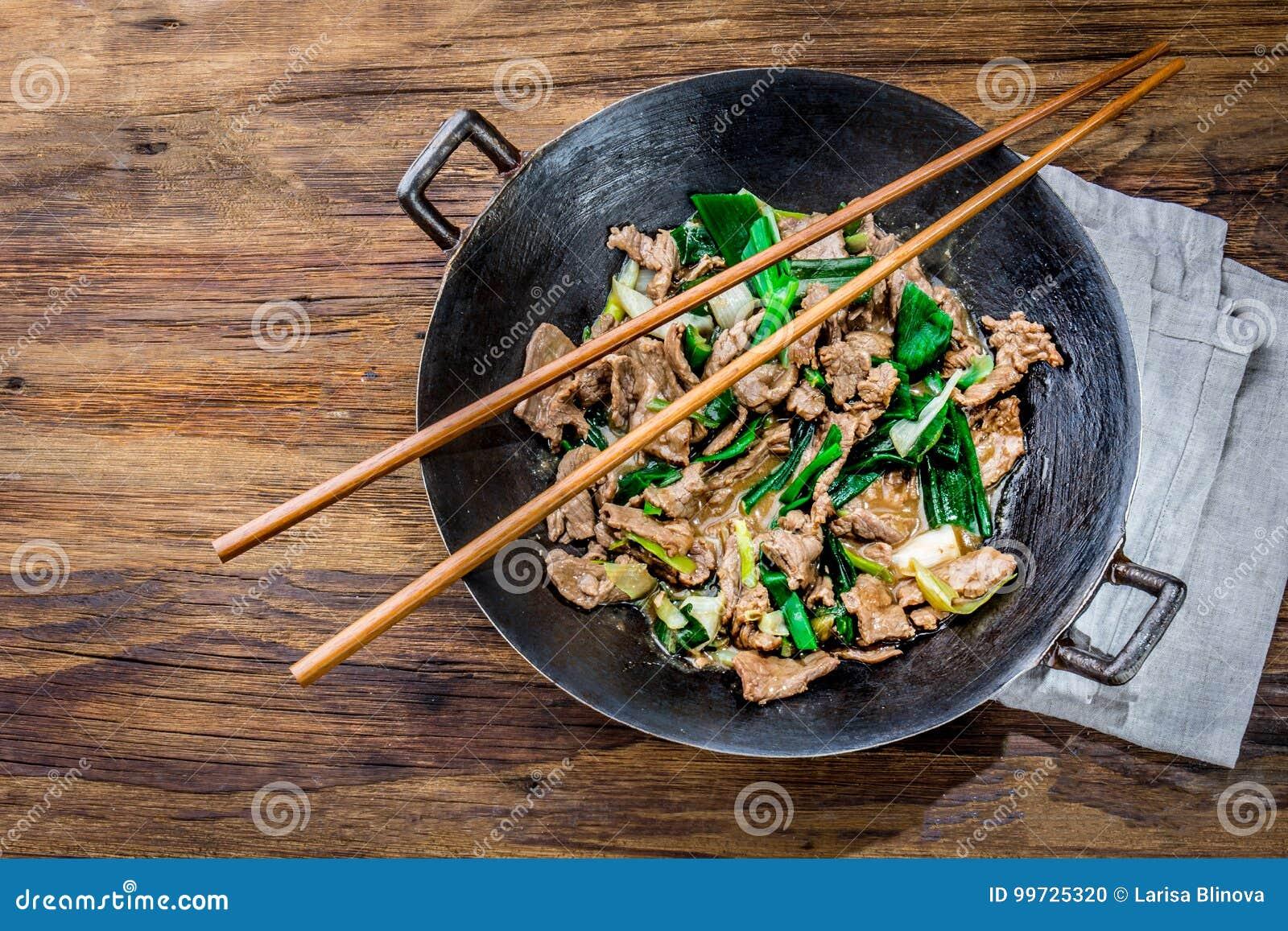 För mongoliannötkött för traditionell kines småfisk för uppståndelse i kinesiskt gjutjärn wokar med matlagningpinnar, träbakgrund