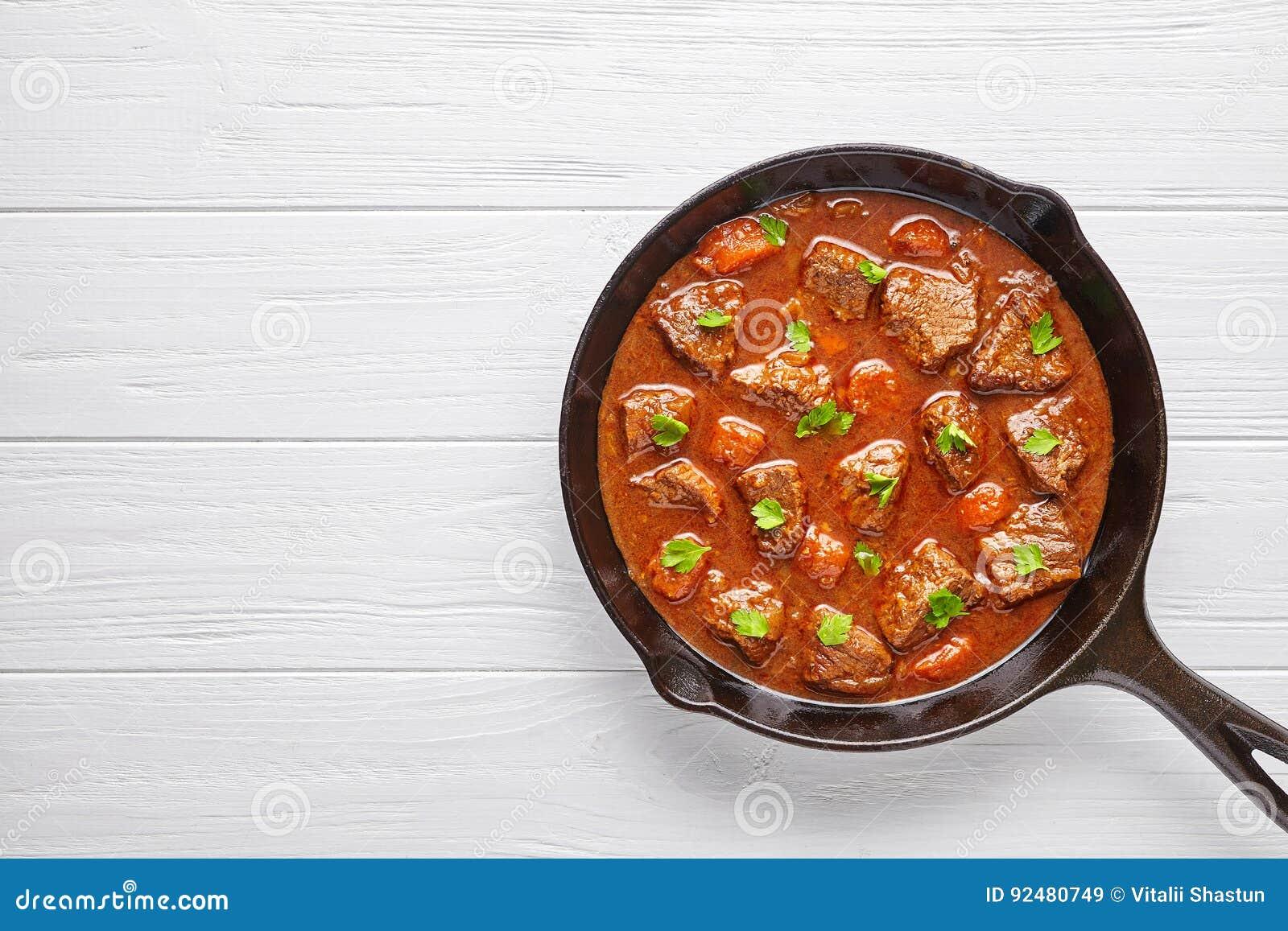 För nötköttkött för gulasch traditionell hemlagad ungersk mat för soppa för ragu med kryddig sky i gjutjärnpannakastrull