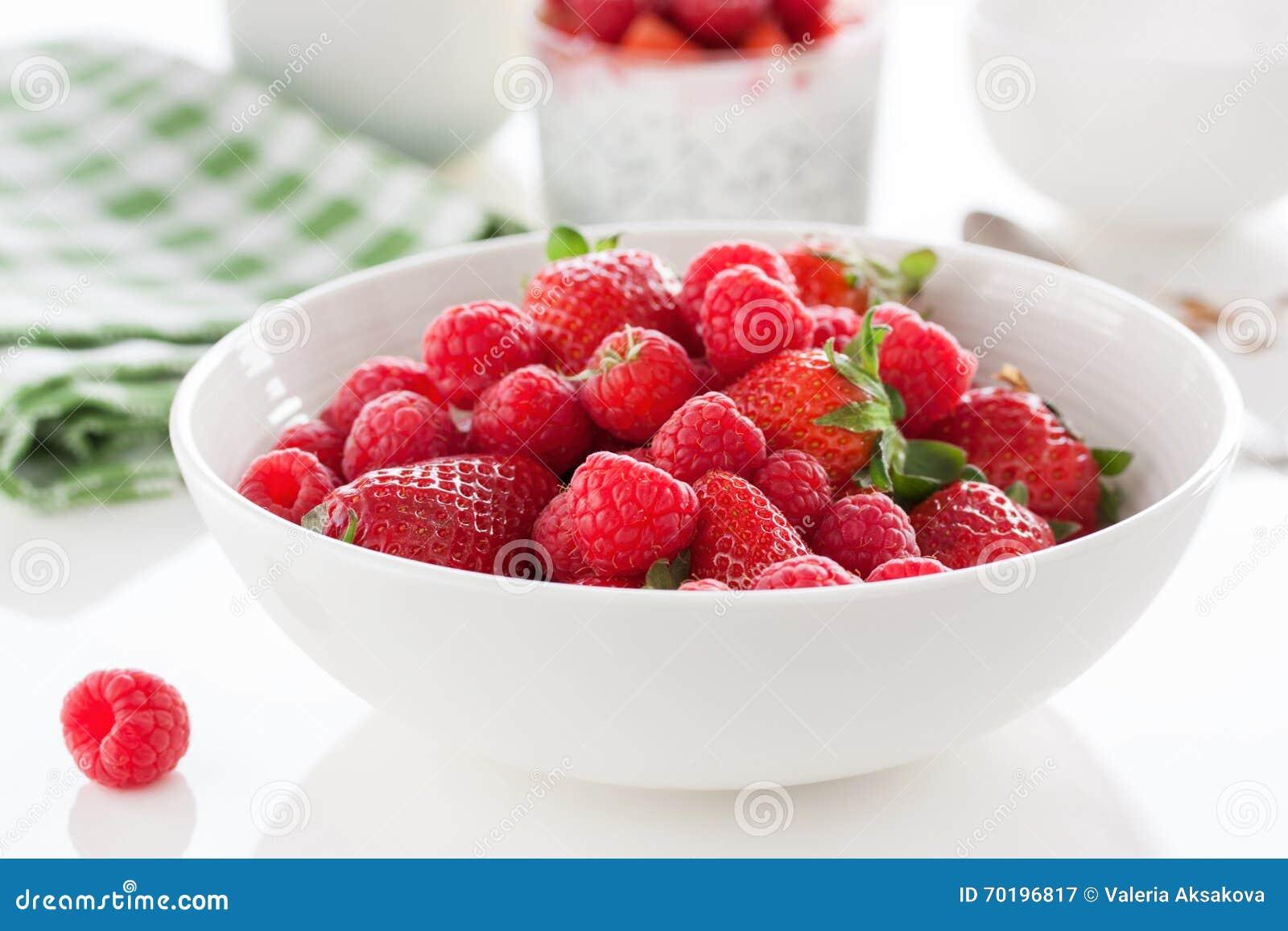 """För ny röd saftig hallon och jordgubbar frukt†för sommar """"i en vit bunke på en tabell för frukost eller lunch"""