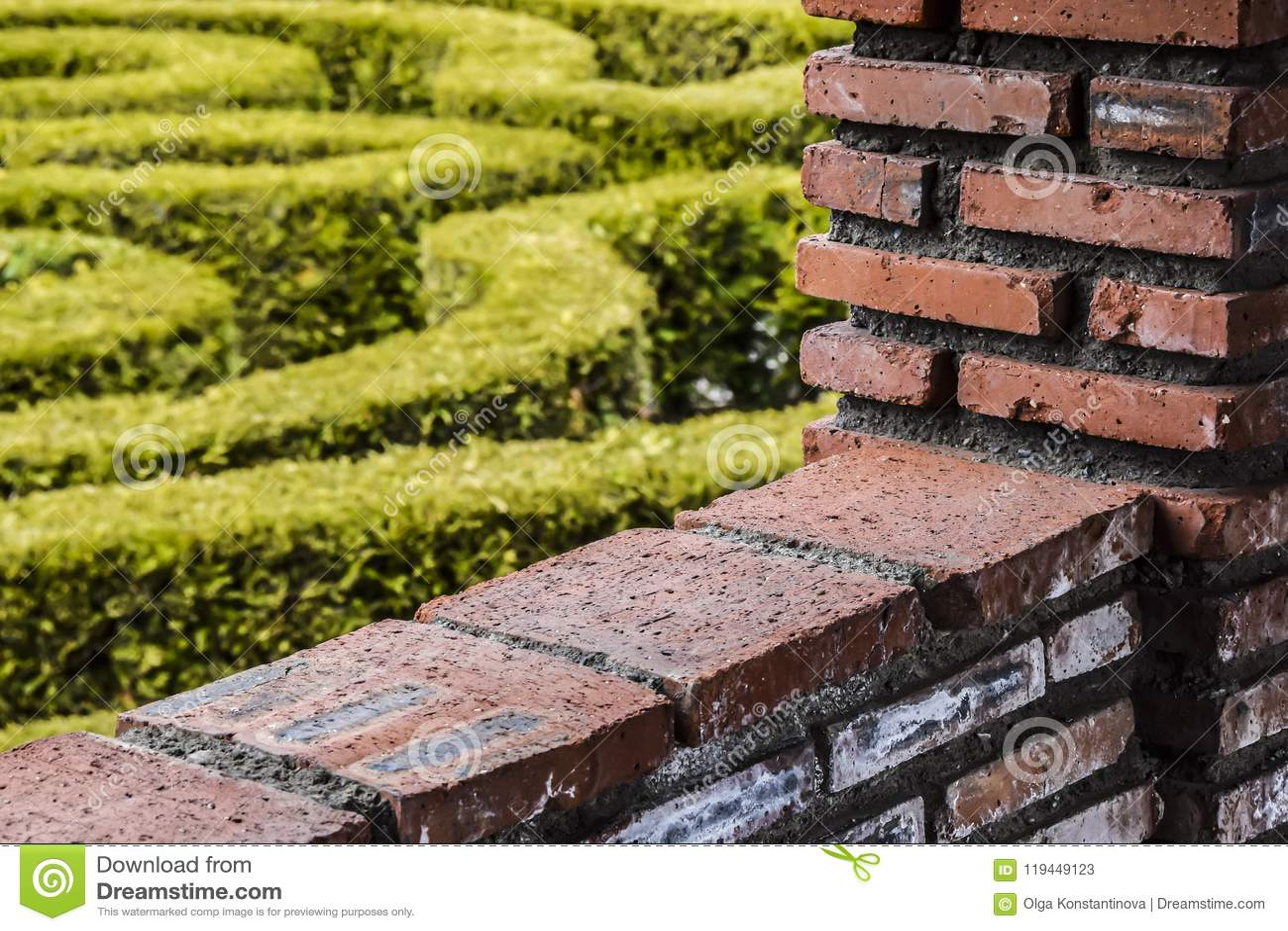 För röd tegelsten för väggen och kontrasterar den trädgårds- bakgrundsabstraktionen för gräsplan