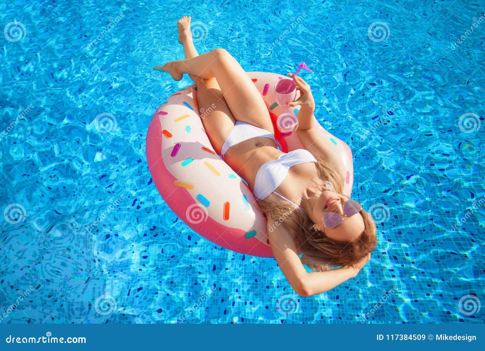 För sommarterritorium för katya krasnodar semester Kvinna i bikini på den uppblåsbara munkmadrassen i SPA simbassängen