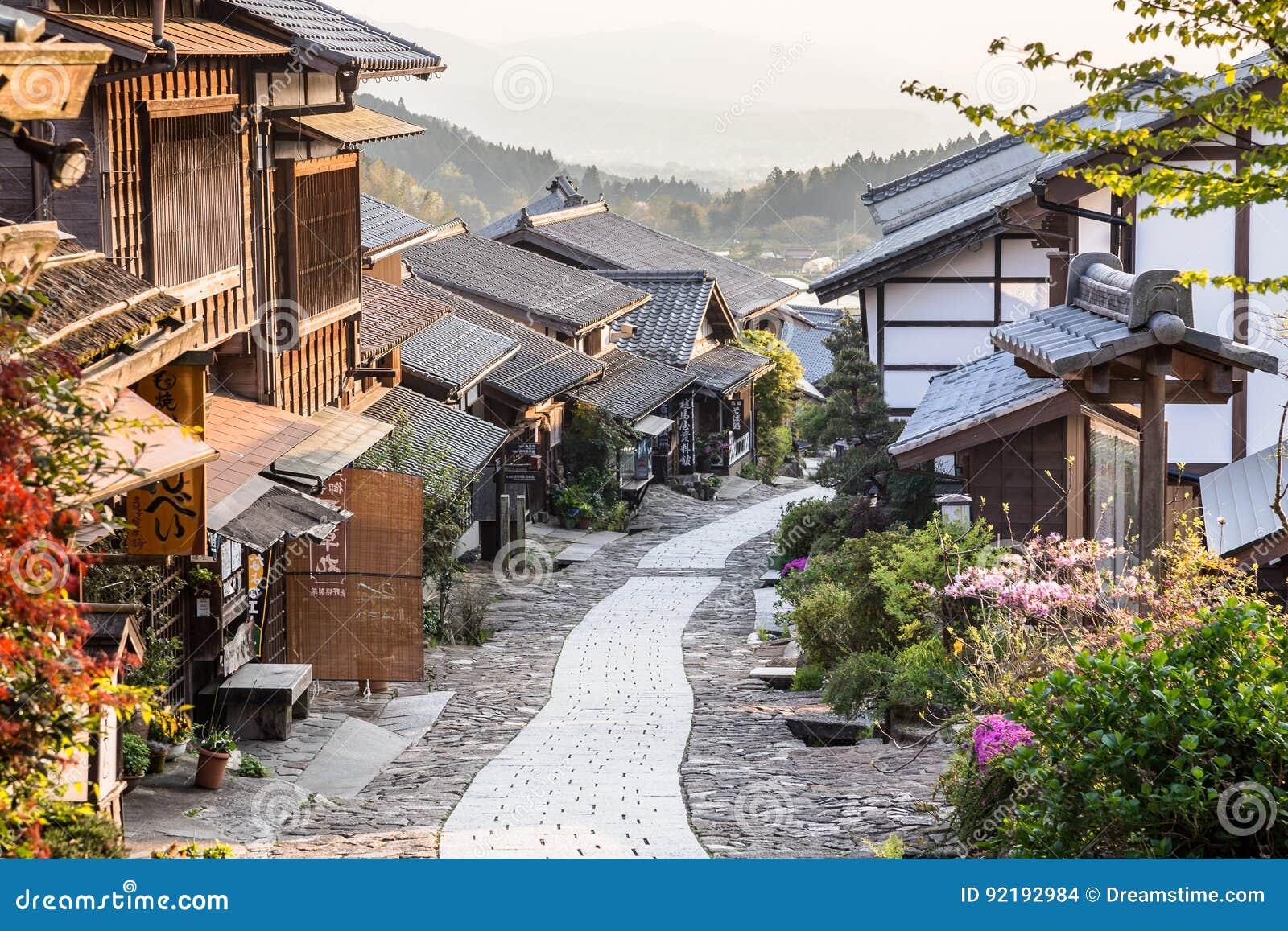 By för stolpe för handel för Japan ` s historisk av Magome på solnedgången i den Kiso dalen
