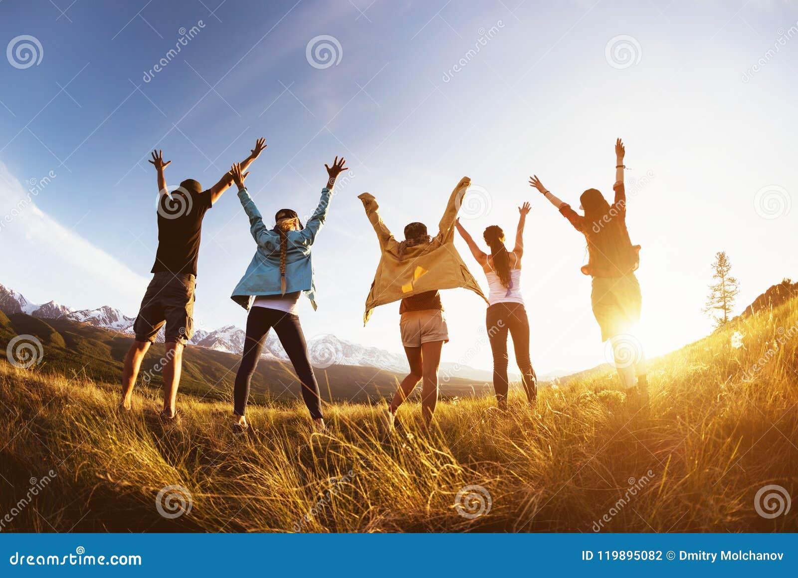 För vänberg för grupp lycklig lyftta armar solnedgång