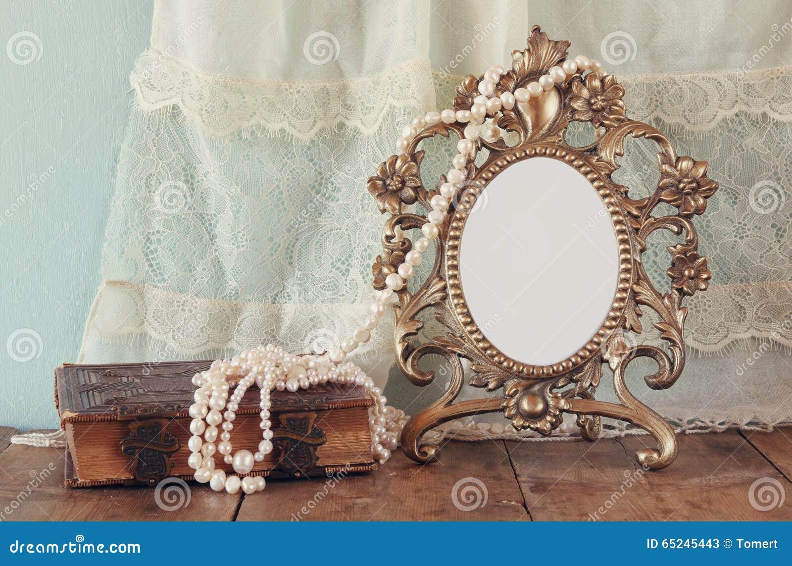 För victorianstil för antikviteten pryder med pärlor den tomma ramen och den gamla boken med tappning halsbandet på trätabellen r