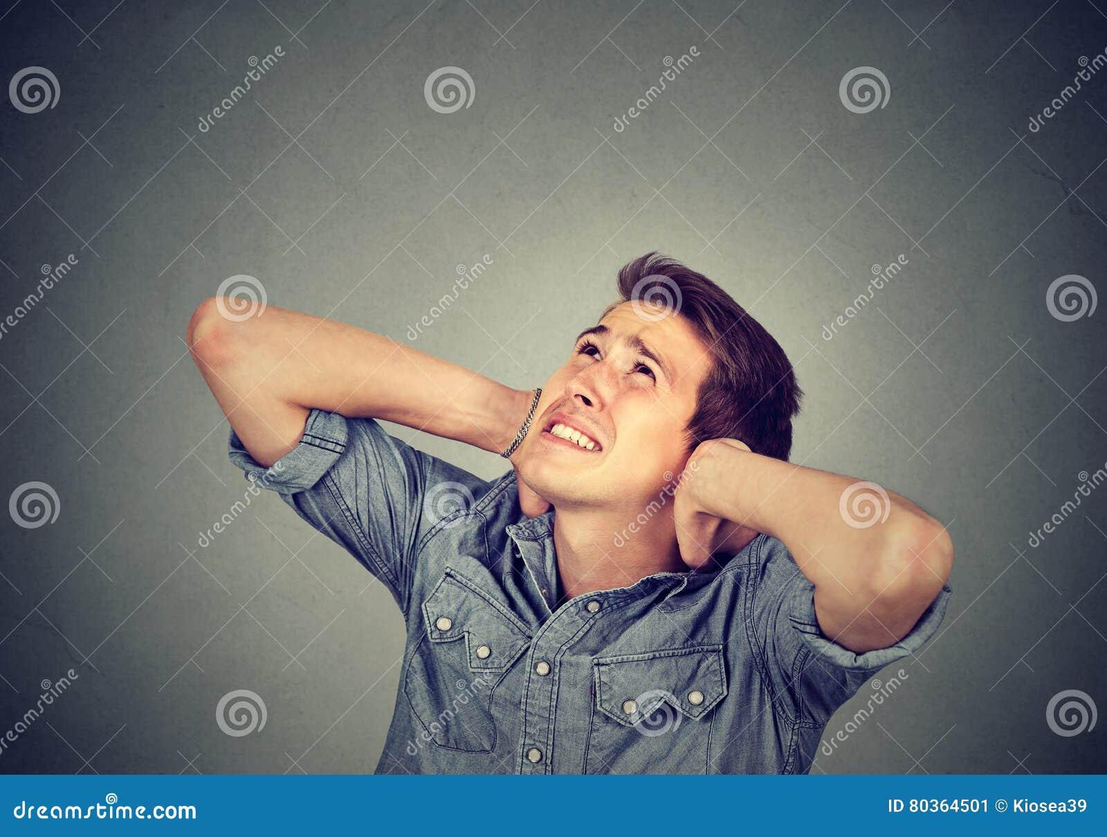 Förargad stressad man som täcker hans öron som ser upp