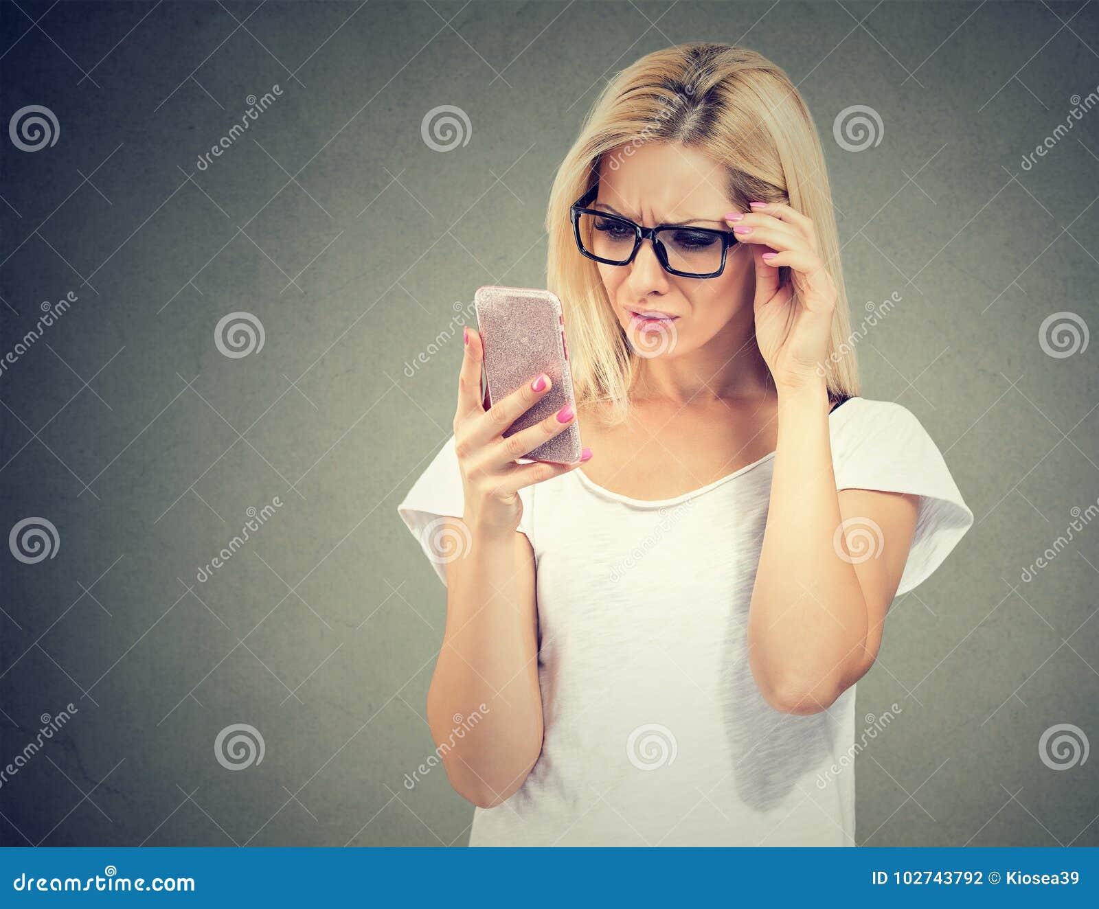 Förargad uppriven kvinna i exponeringsglas som ser hennes mobiltelefon med frustration