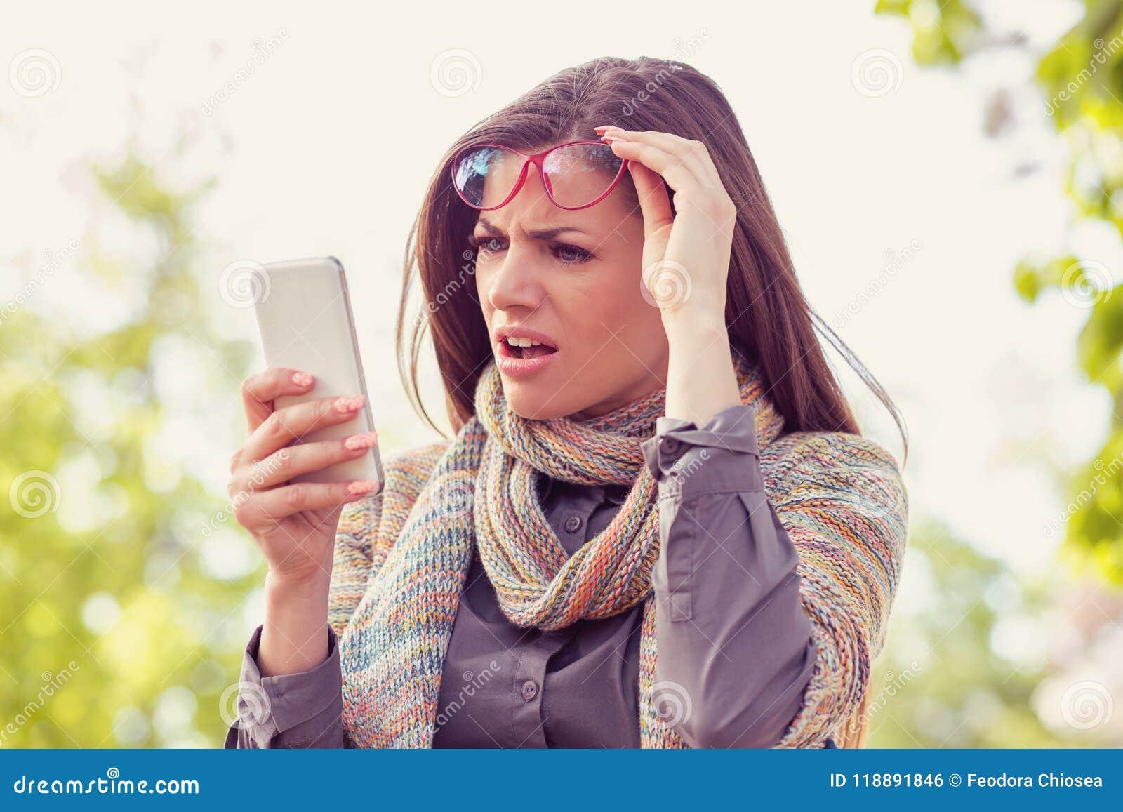 Förargad uppriven kvinna i exponeringsglas som ser hennes smarta telefon med frustration, medan gå på en gata