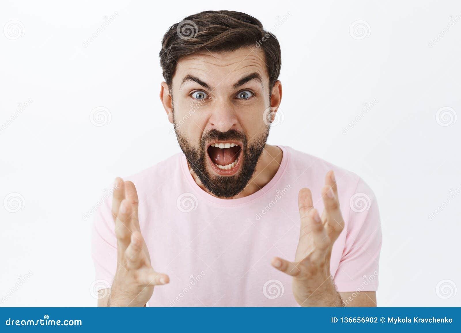 Förbannad grabb som skriker från ilska och hat under argument Stående av den grovt förolämpa pressade caucasian mannen med skägge