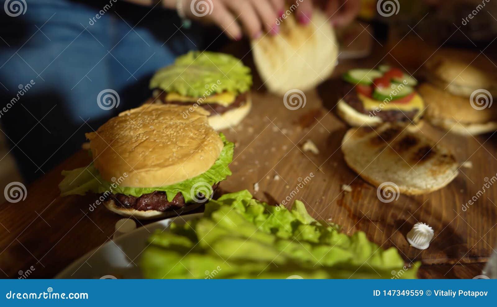 Förbereda hamburgare som gör hamburgaren, ingredienser för att laga mat hamburgare, grönsaker, ost och grönsaker på tabellen