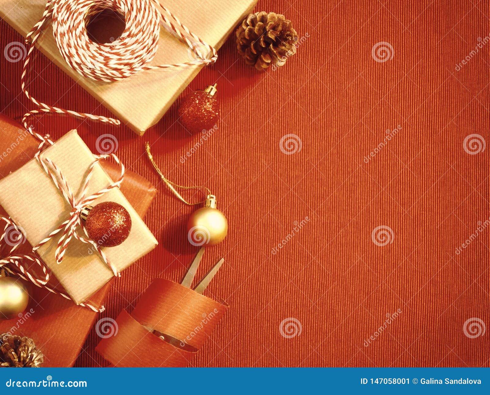 Förbereda sig för ferien - inpackning av jul- eller julgåvor i rött och beige inpackningspapper