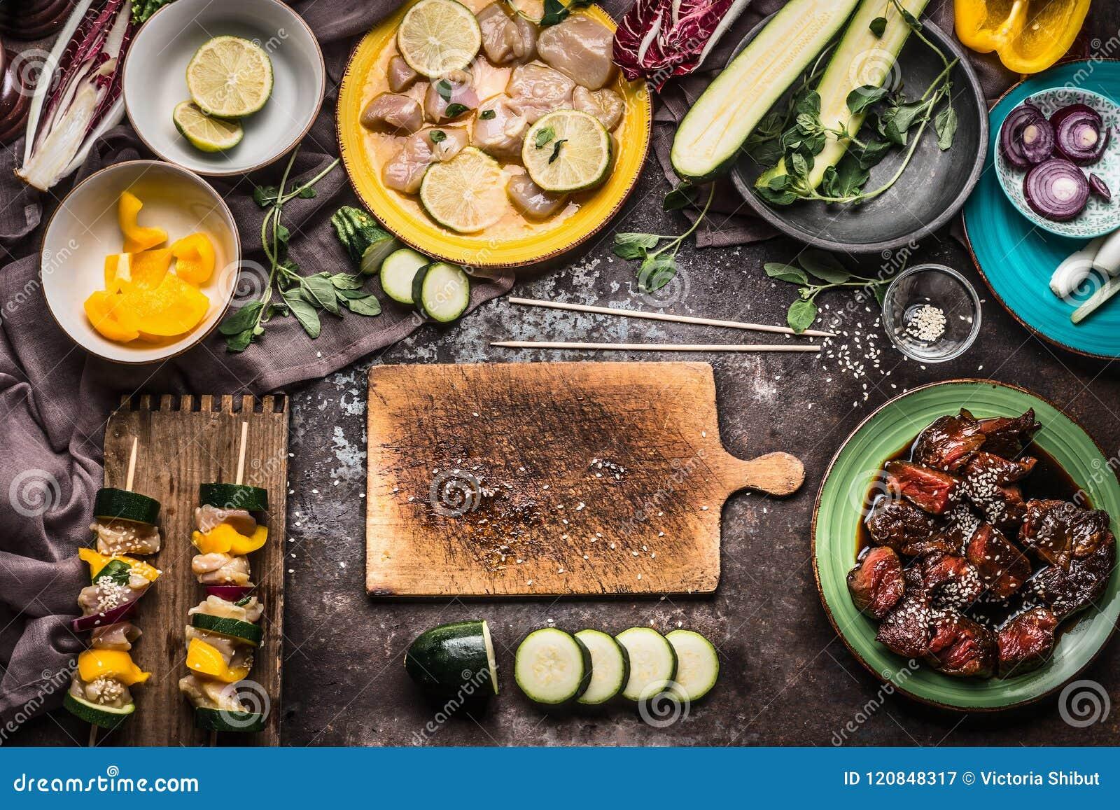 Förberedelse av olika hemlagade köttgrönsaksteknålar för galler eller bbq på lantlig bakgrund med ingredienser