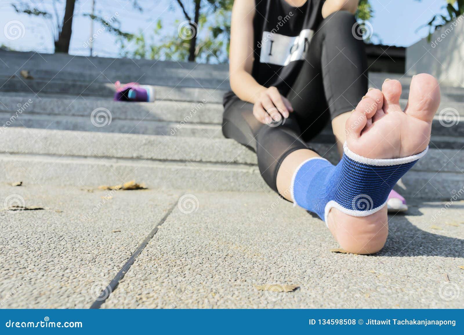 Förbinder kvinnlig användande resår för handen med ben, kvinnligt sätta förbinder på hennes sårade fot från sport