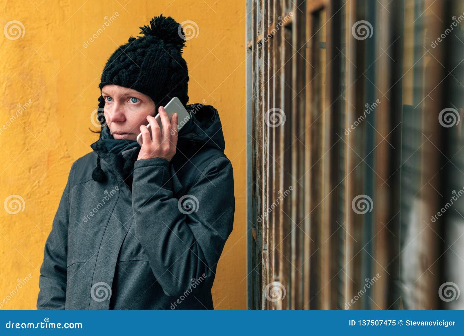 Förbittrad kvinna under påringning på gatan i vinter